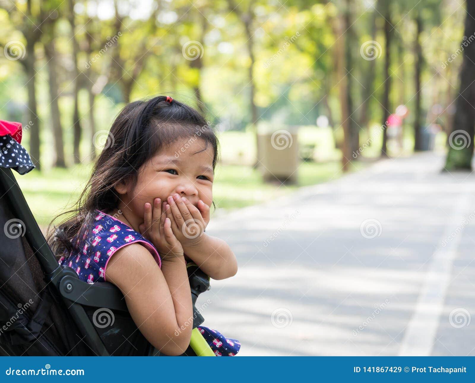 Menina asiática pequena que senta-se em um carrinho de criança no parque público Olha happly e rir e amordaçar
