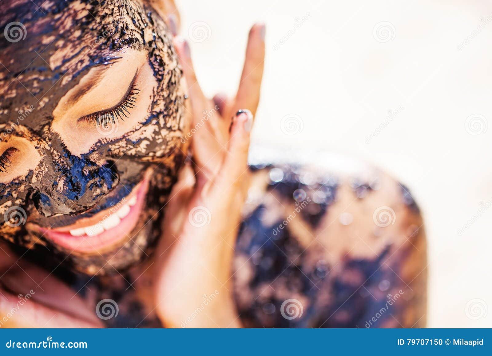 Menina asiática que aplica a máscara protetora do chocolate