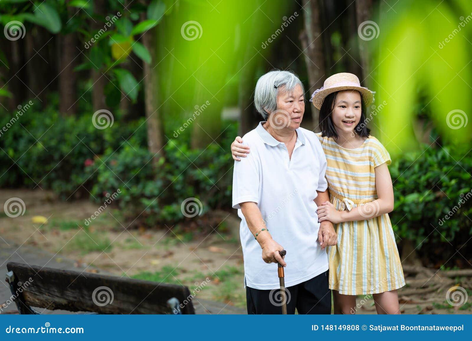 Menina asiática que apoia a mulher superior com vara de passeio, a avó de sorriso feliz e a neta no parque, idoso