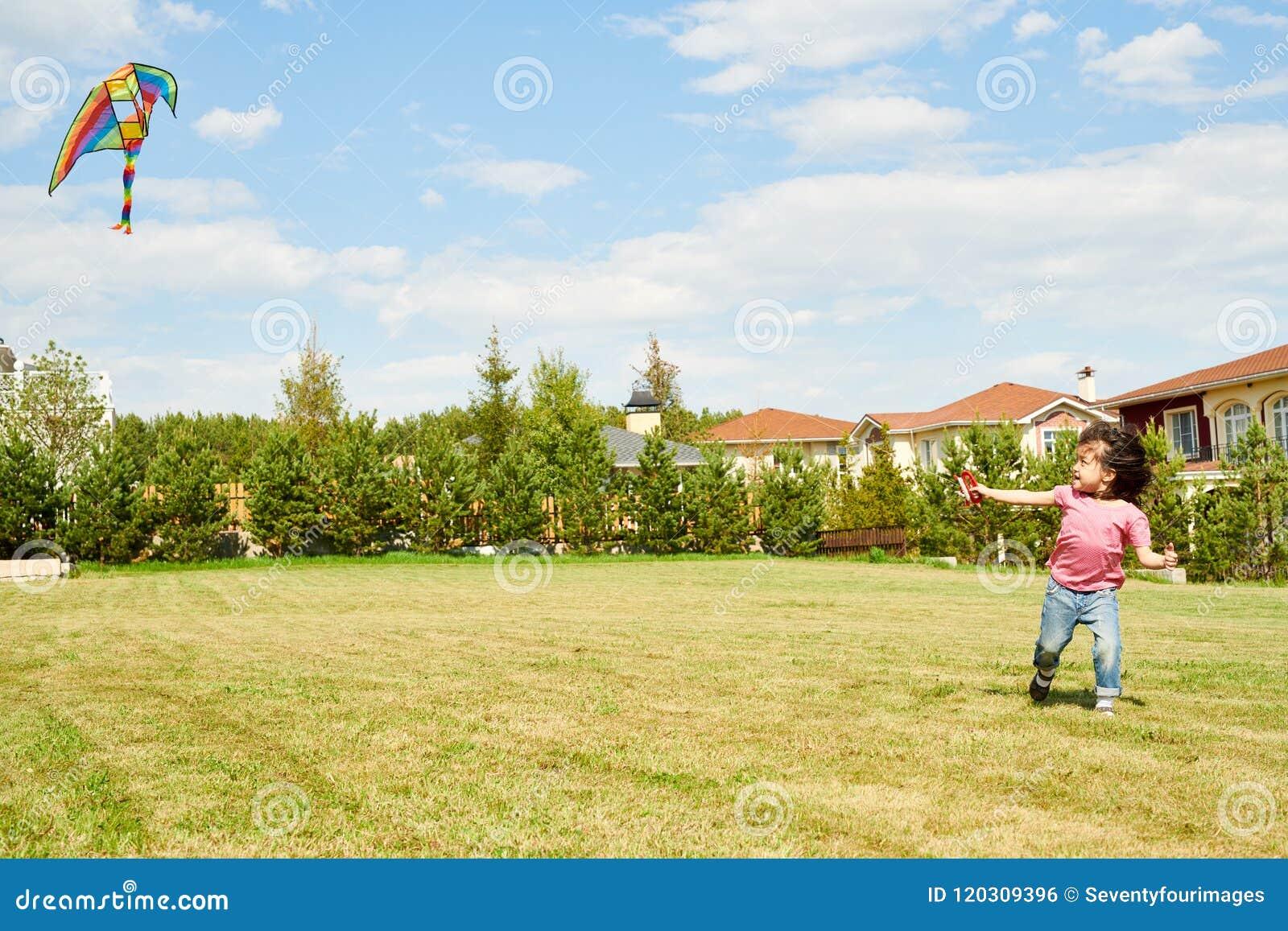 Menina asiática que corre com papagaio