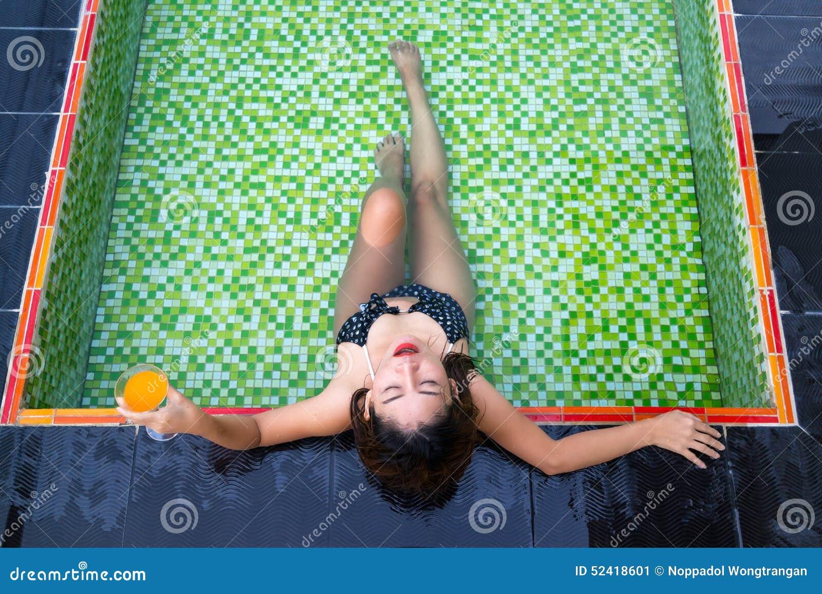 Menina asiática que guarda o vidro do suco de laranja em suas mãos que encontram-se na piscina