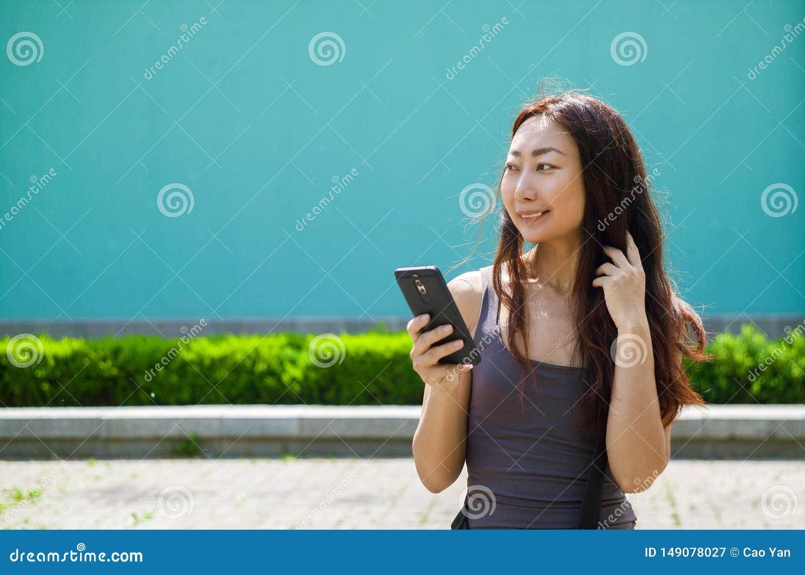 A menina asi?tica de sorriso feliz com telefone celular l? a mensagem, fundo azul