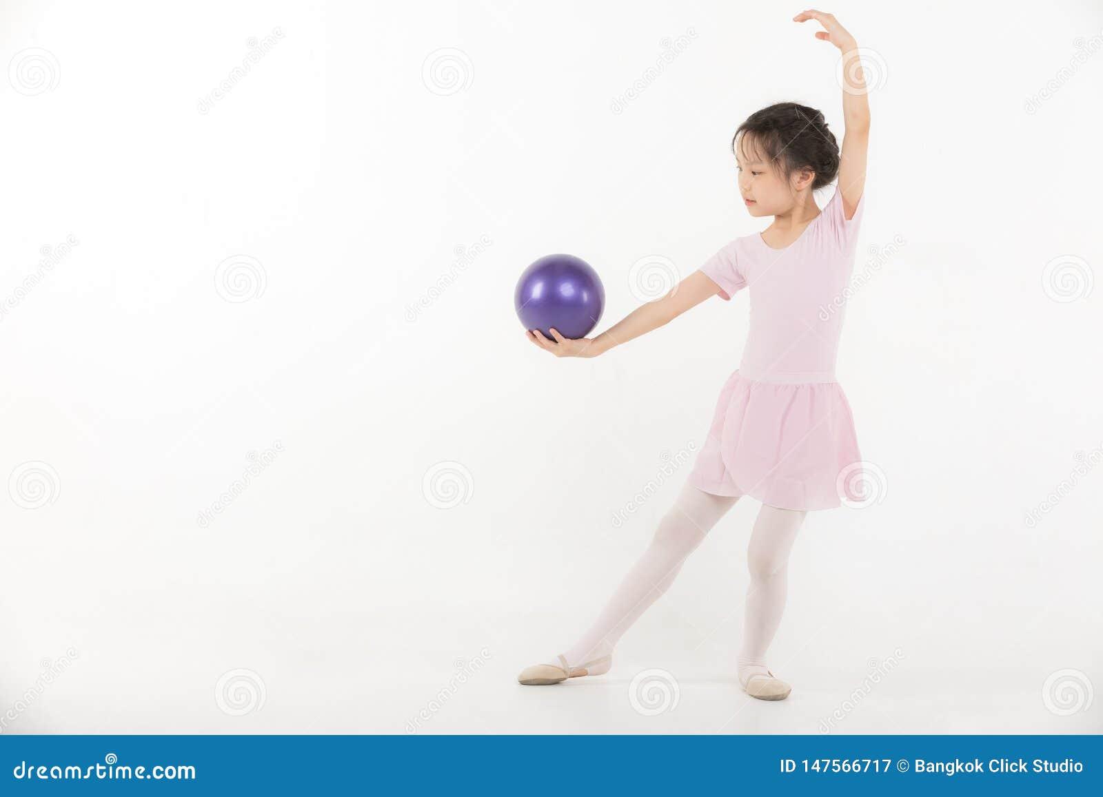 A menina asi?tica no vestido cor-de-rosa est? guardando a bola