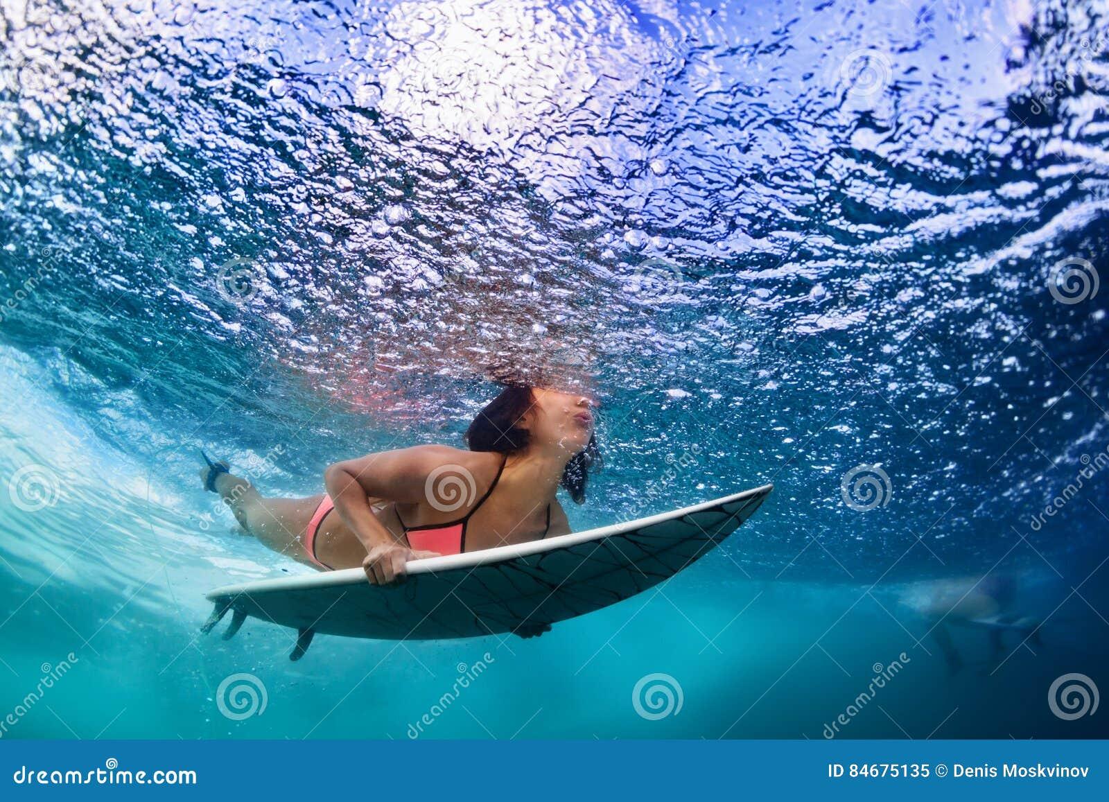 Menina ativa no biquini na ação do mergulho na placa de ressaca