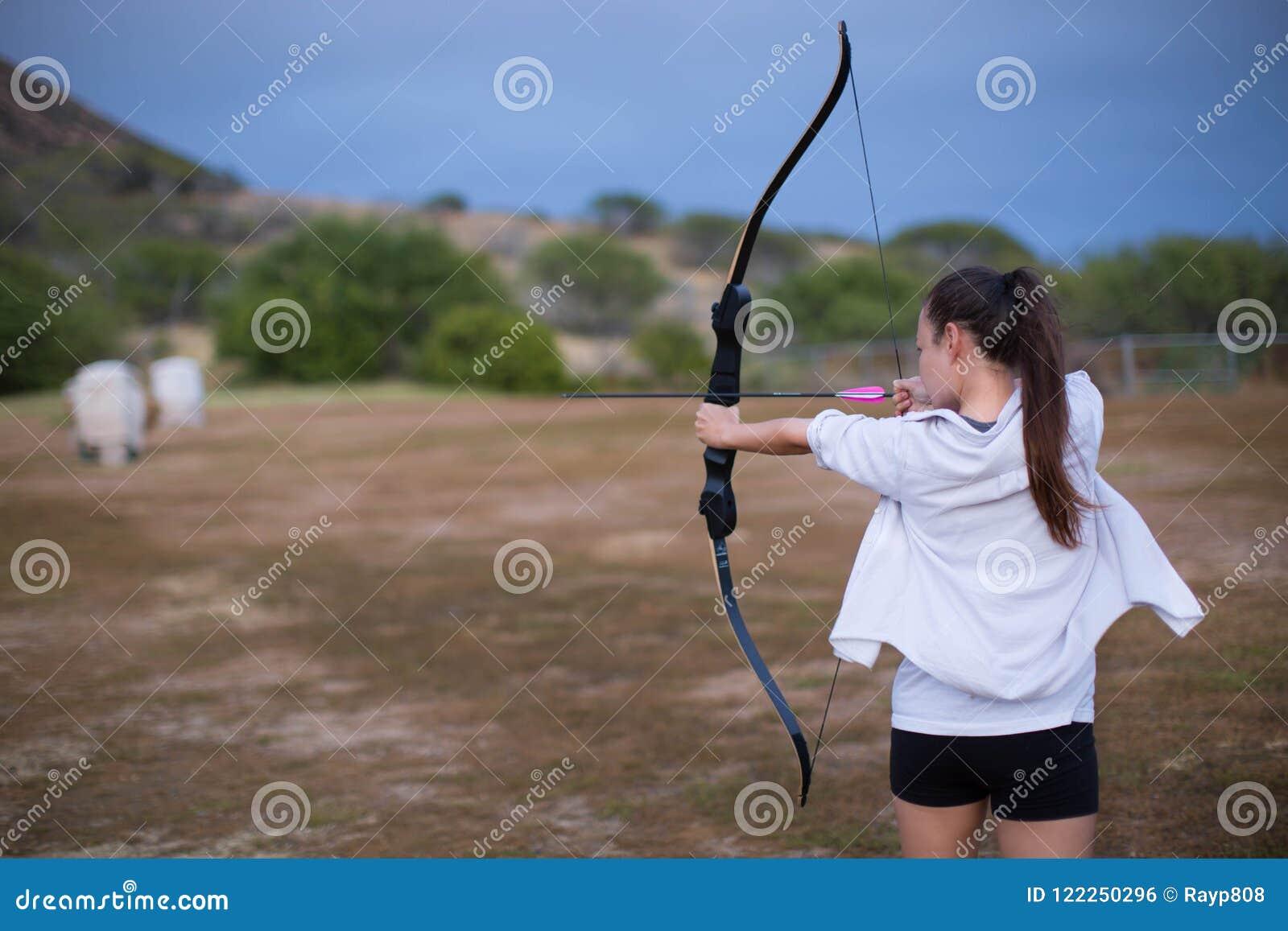 Menina atlética e atlética que aponta uma curva e uma seta em uma escala do tiro ao arco