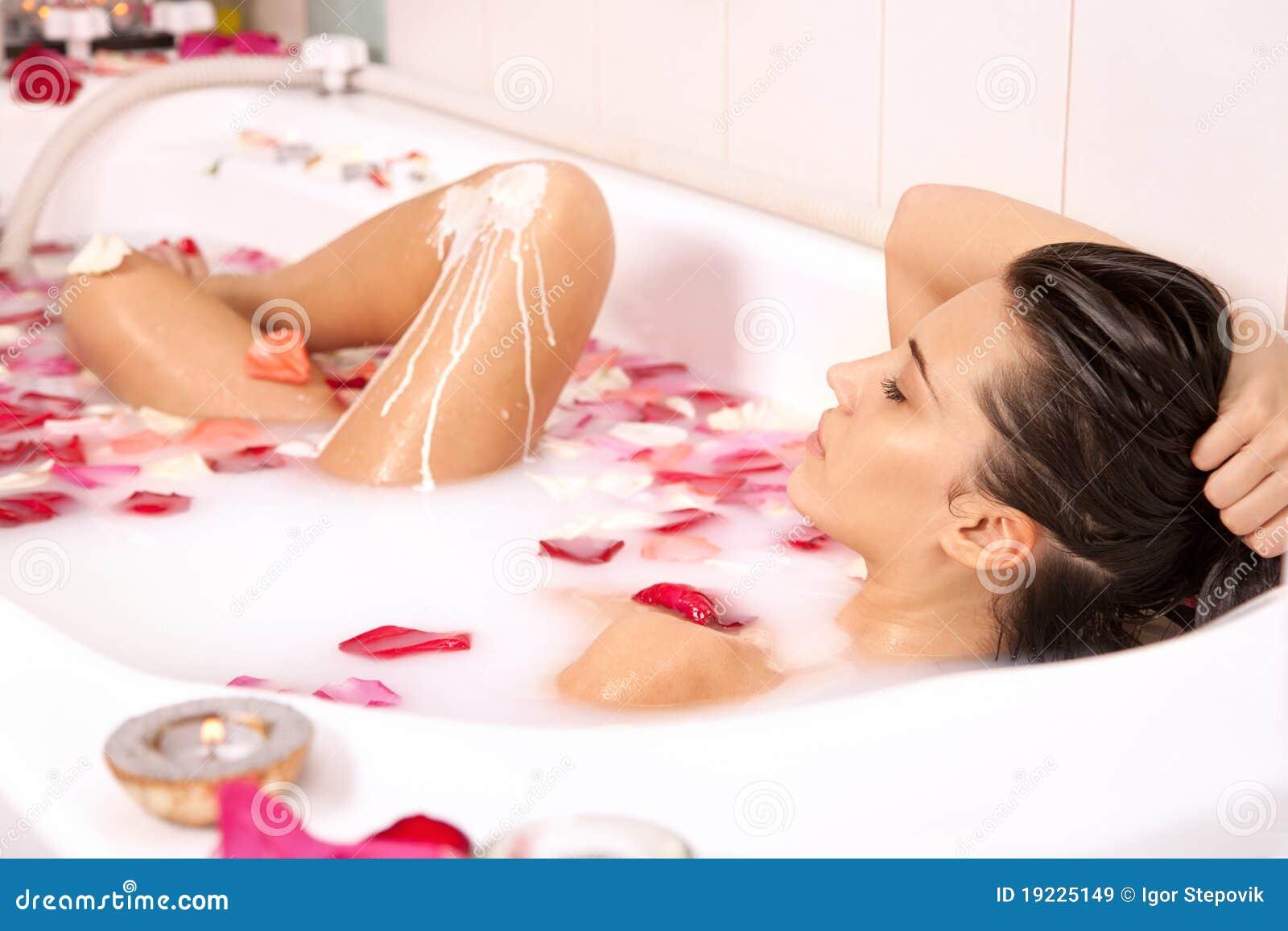 A menina atrativa aprecia um banho com leite e rosas