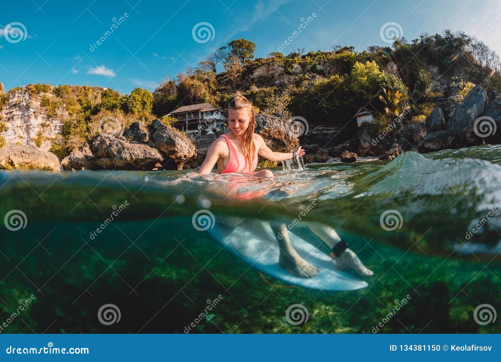 Menina atrativa do surfista com prancha O surfista senta-se na placa no oceano