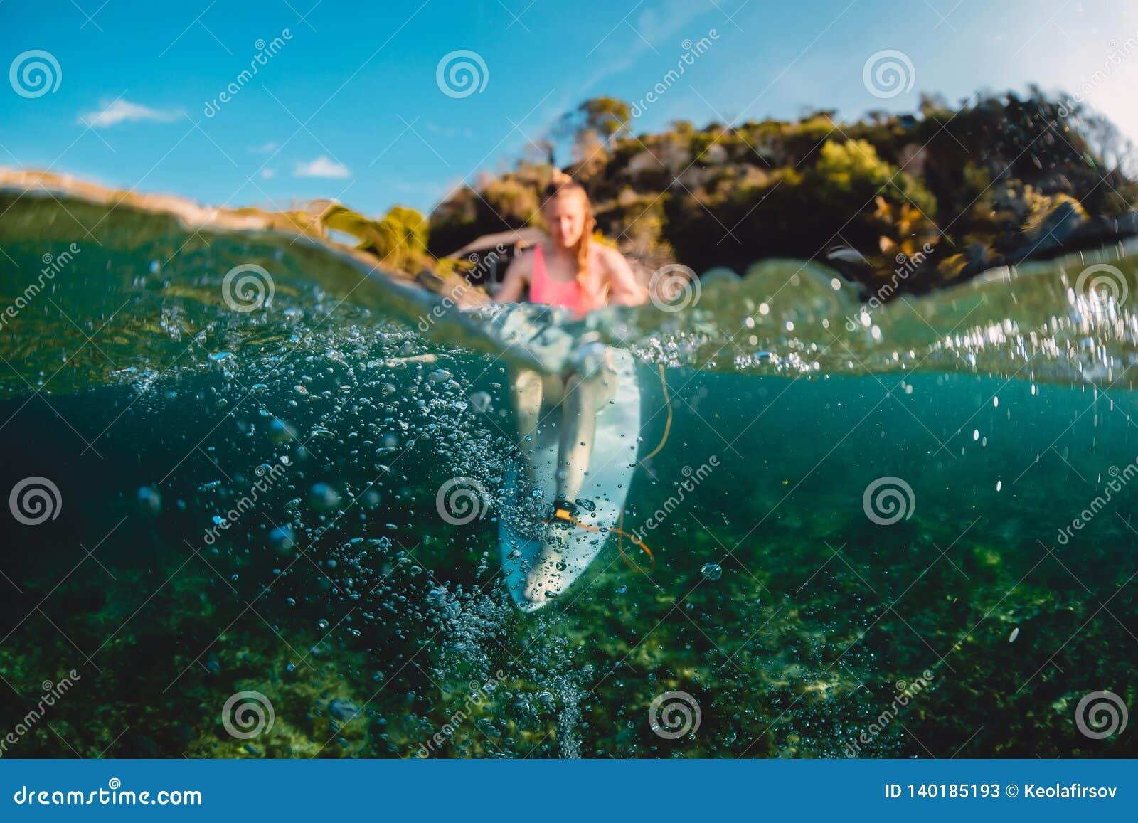 Menina atrativa do surfista com prancha O surfista senta-se na placa