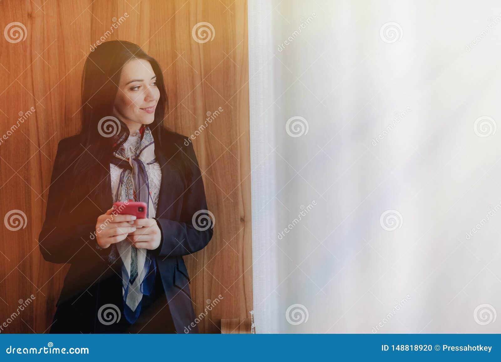 Menina atrativa emocional nova na roupa do neg?cio-estilo em uma janela com um telefone em um escrit?rio ou em um audit?rio moder