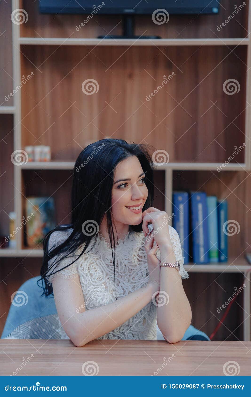 Menina atrativa emocional nova que senta-se em uma mesa em um escrit?rio ou em um audit?rio moderno