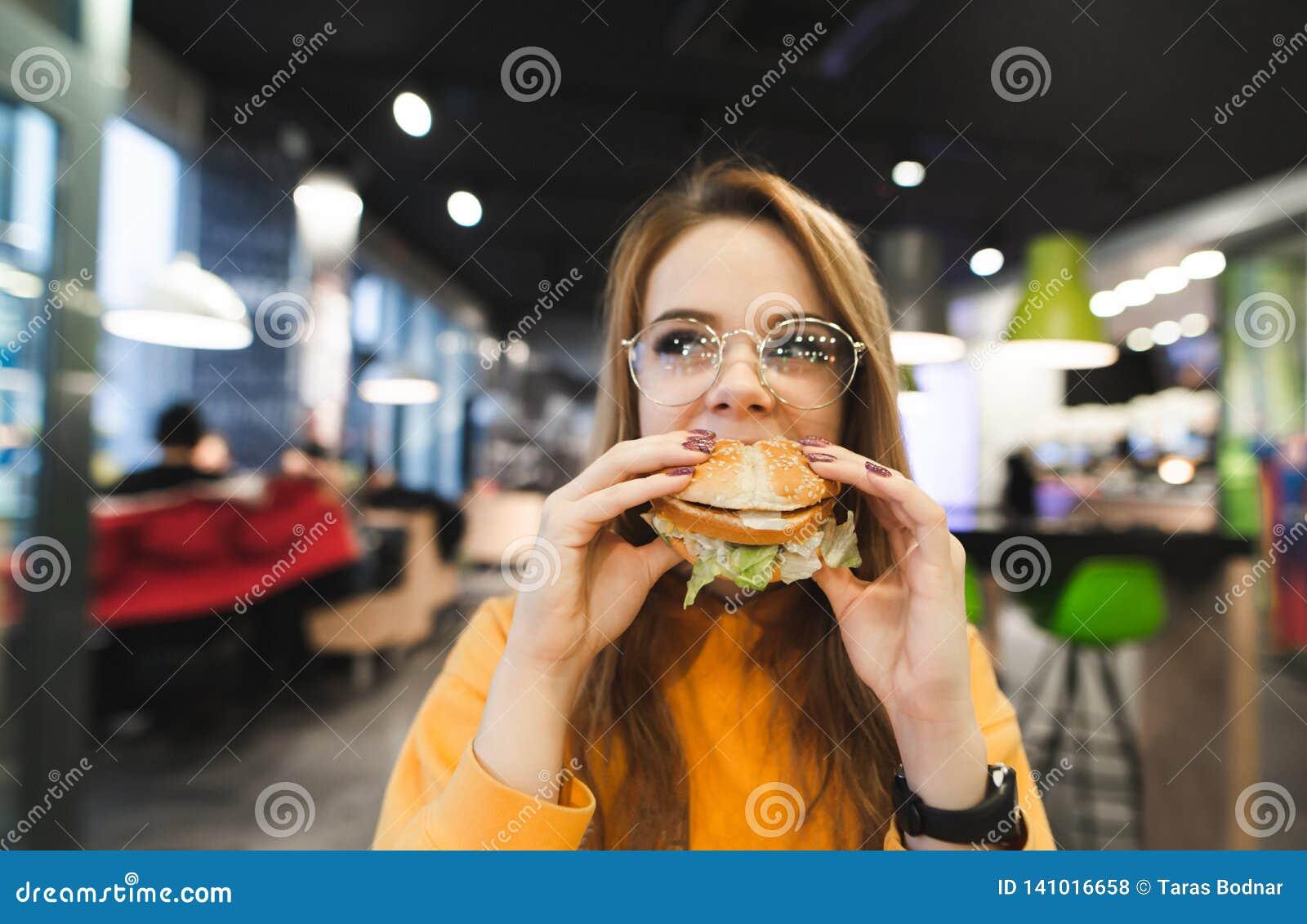 A menina atrativa na roupa e em vidros alaranjados senta-se em um restaurante de comida rápida e come-se um grande hamburguer ape
