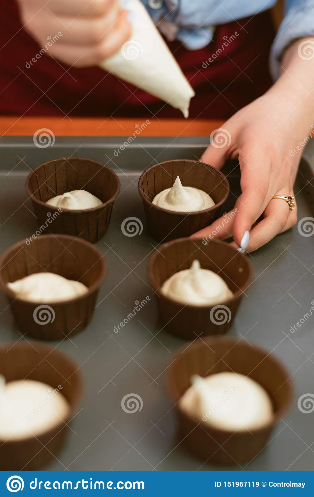 Menina atrativa que faz queques, foto da opinião lateral do close up a mulher aprende fazer queques