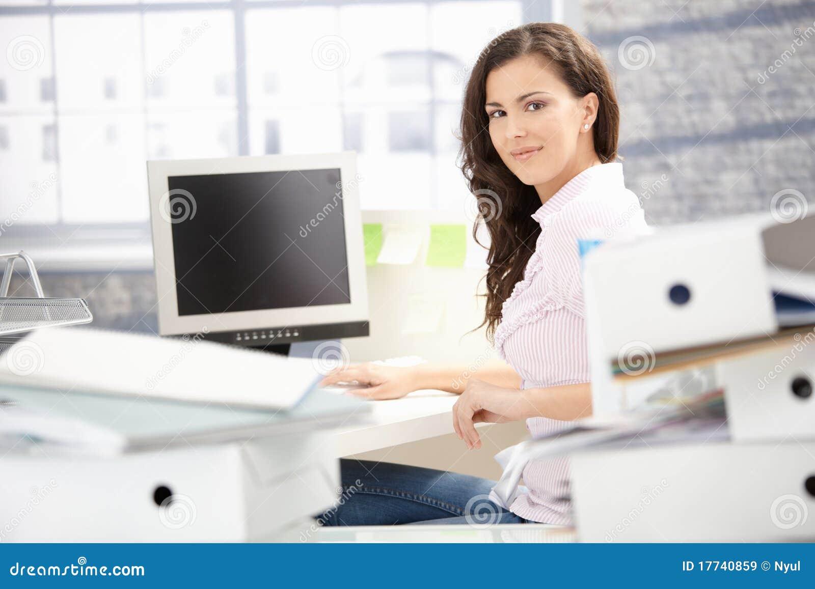 Menina atrativa que trabalha no sorriso brilhante do escritório