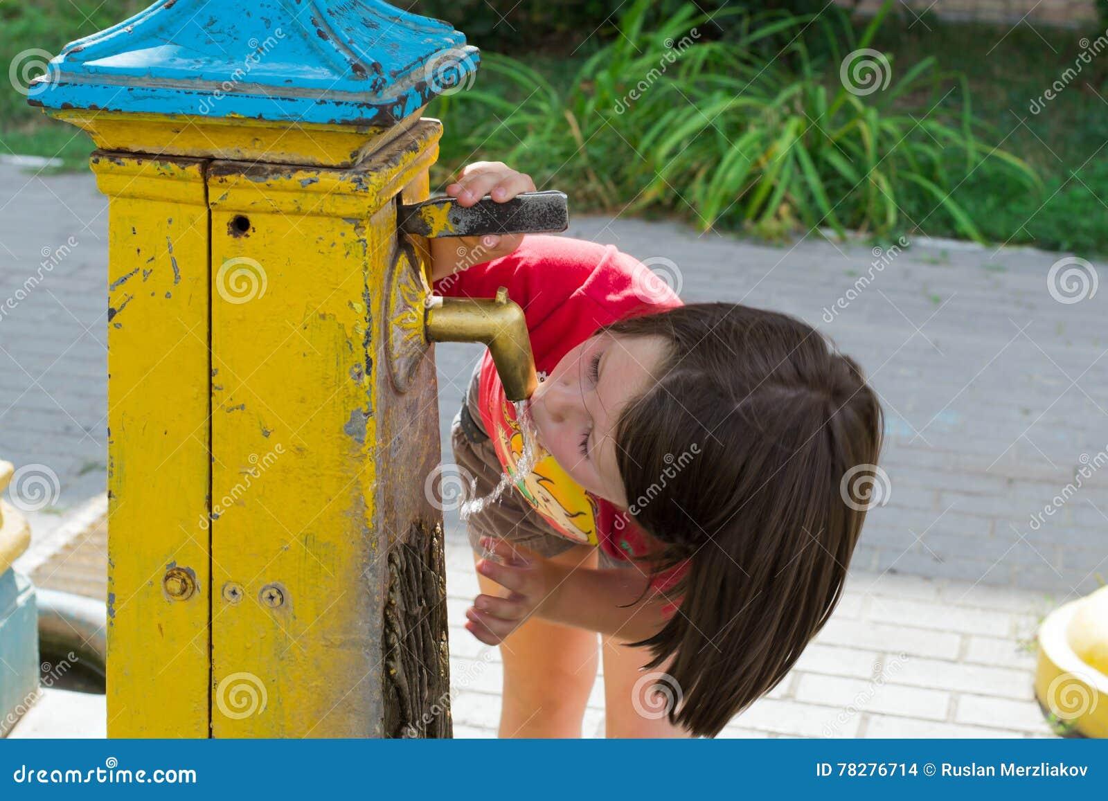 A menina bebe a água de um poço