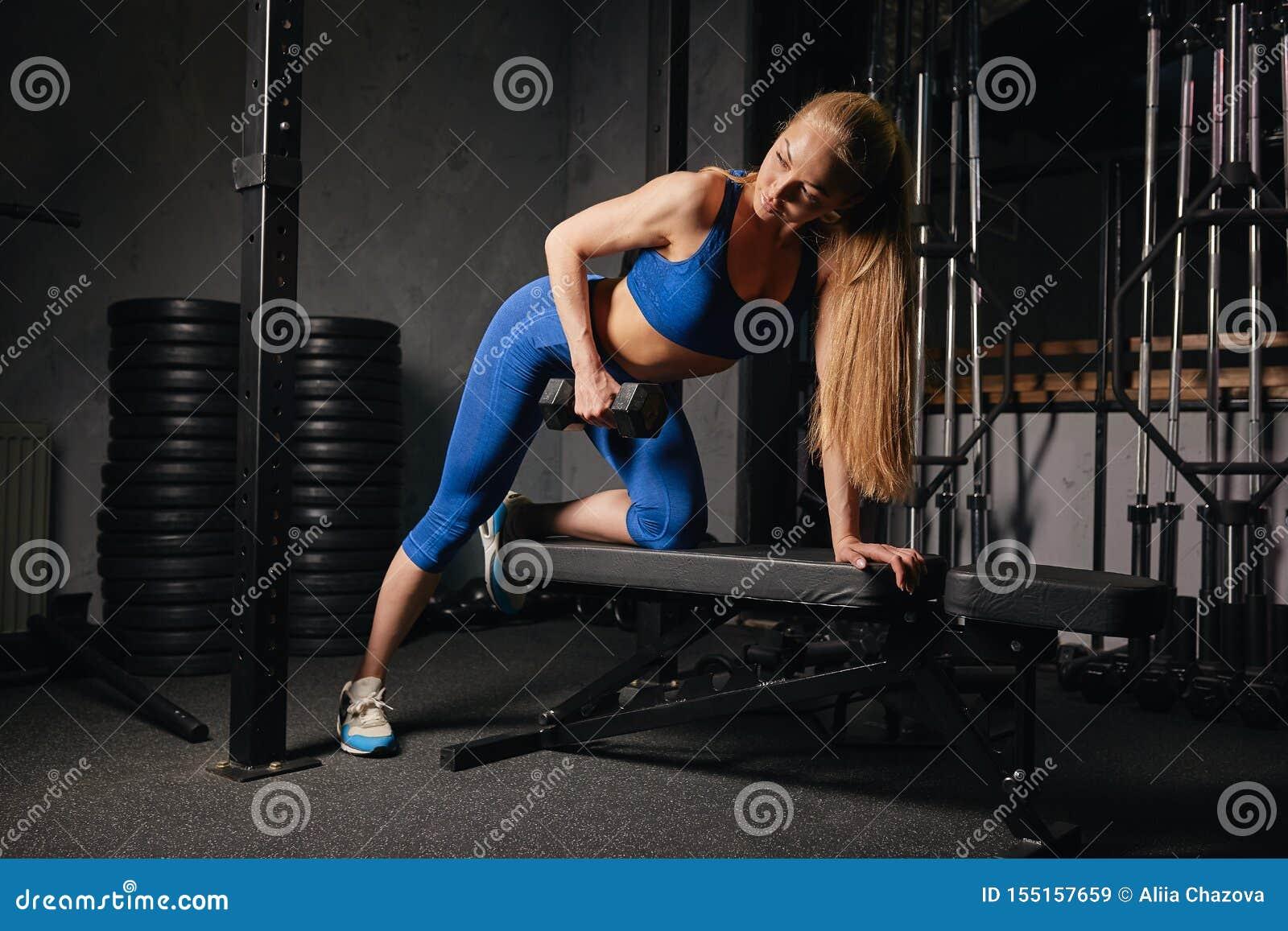 Menina bem-construída bonita no treinamento à moda do sportswear da forma no gym