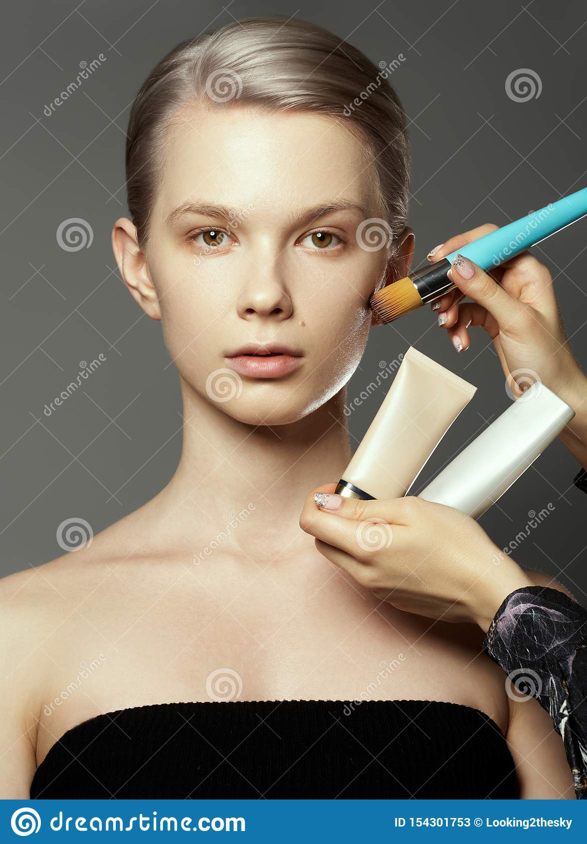 Menina bonita cercada pelas m?os dos maquilhadores com escovas e pelo batom perto de sua cara Foto da mulher feliz sobre