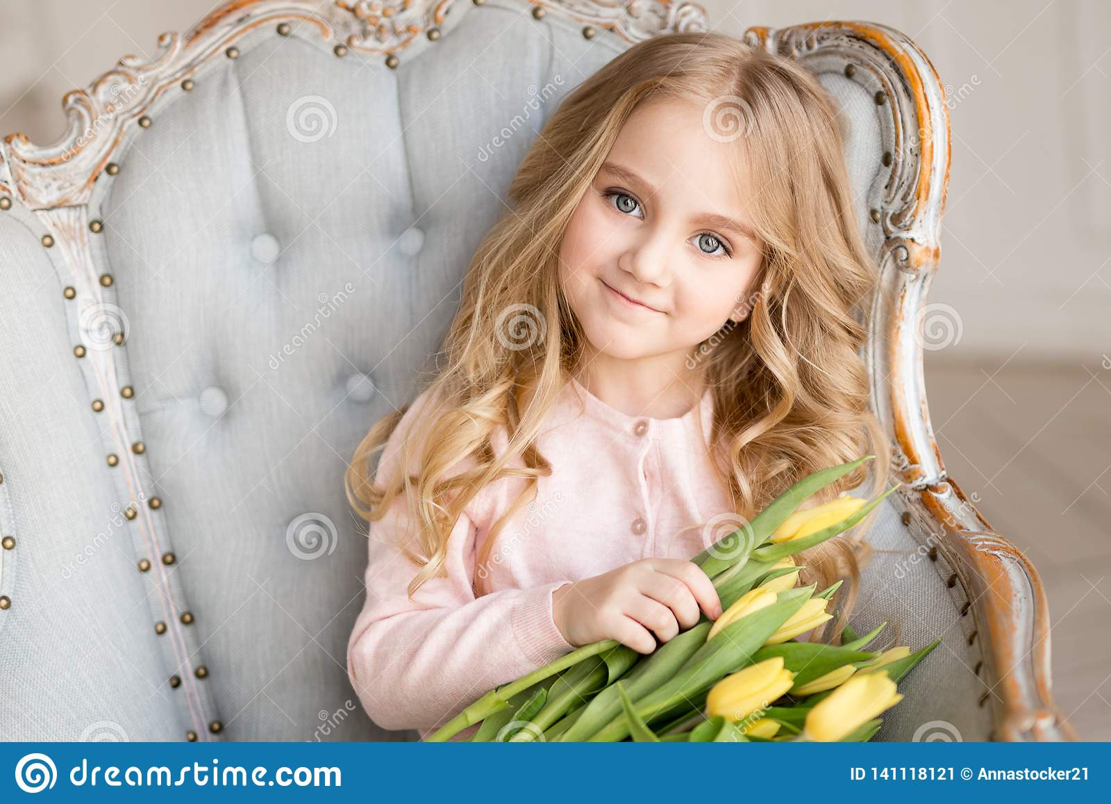 Menina bonita bonita com as tulipas amarelas das flores que sentam-se na poltrona, sorrindo Foto interna