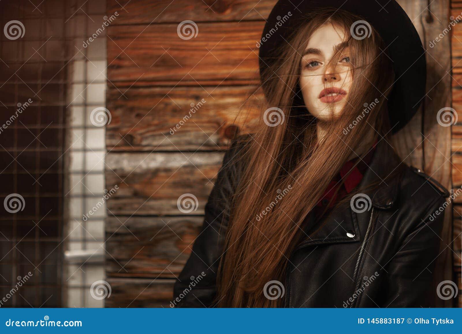 Menina bonita com cabelo e o chap?u negro longos, suportes no fundo da casa de madeira velha do vintage
