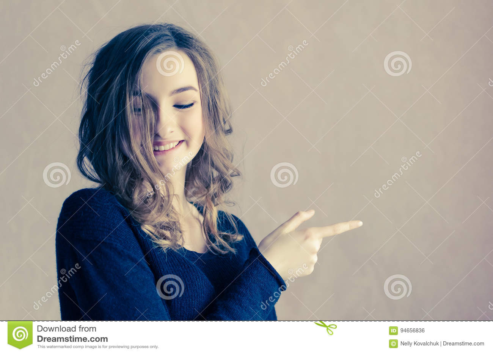 Menina bonita com cabelo encaracolado que aponta ao lado