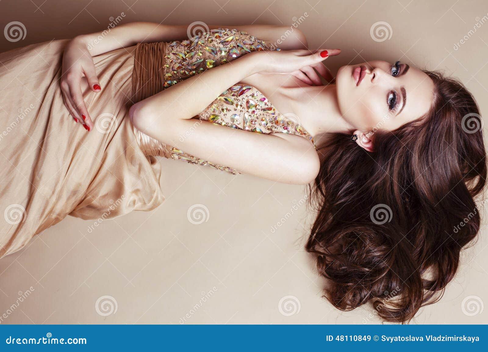 Menina bonita com cabelo escuro luxuoso no vestido da lantejoula que levanta no estúdio