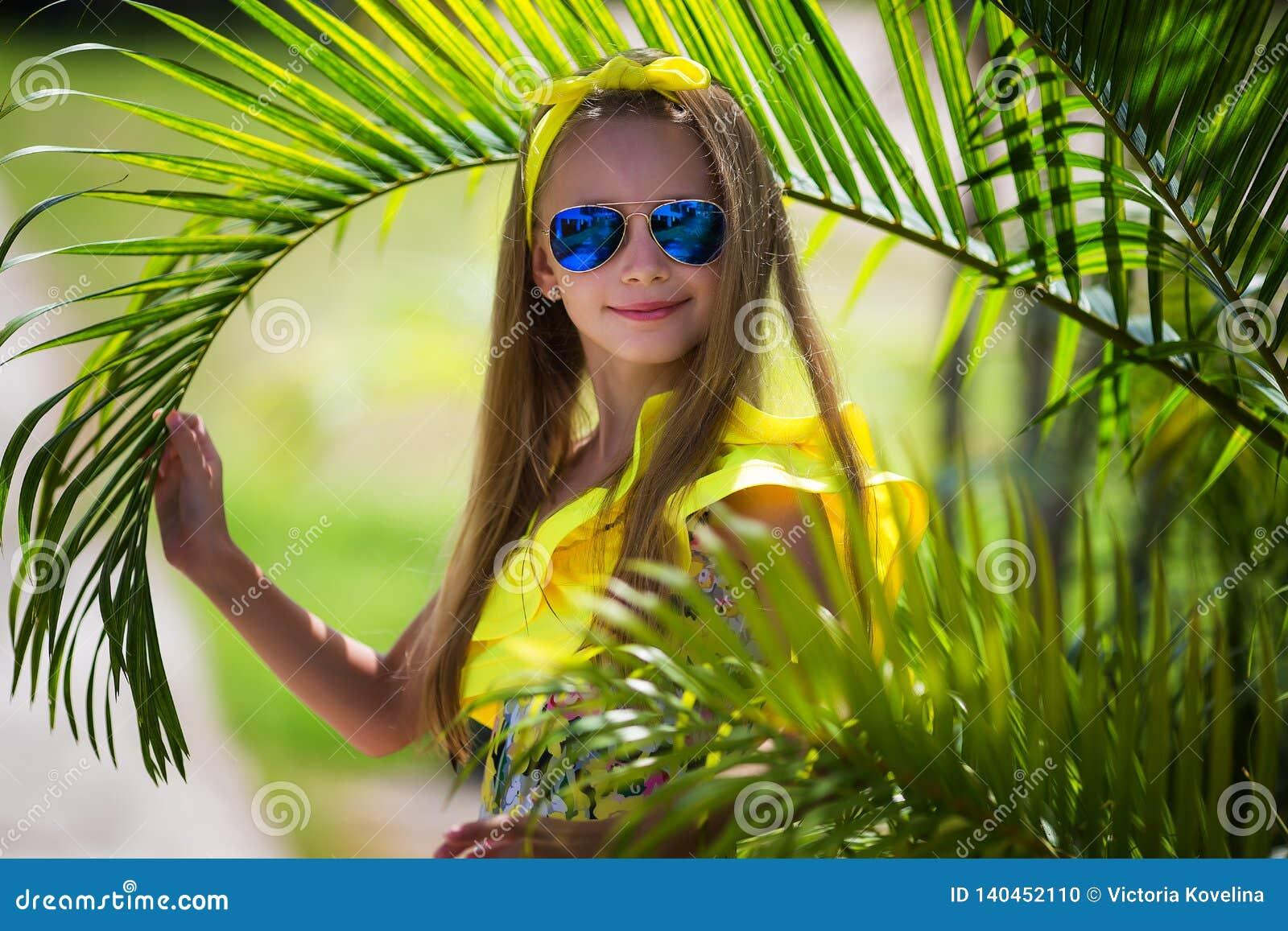 Menina bonita com cabelo longo em um roupa de banho amarelo e em uns óculos de sol multi-coloridos no fundo das palmeiras