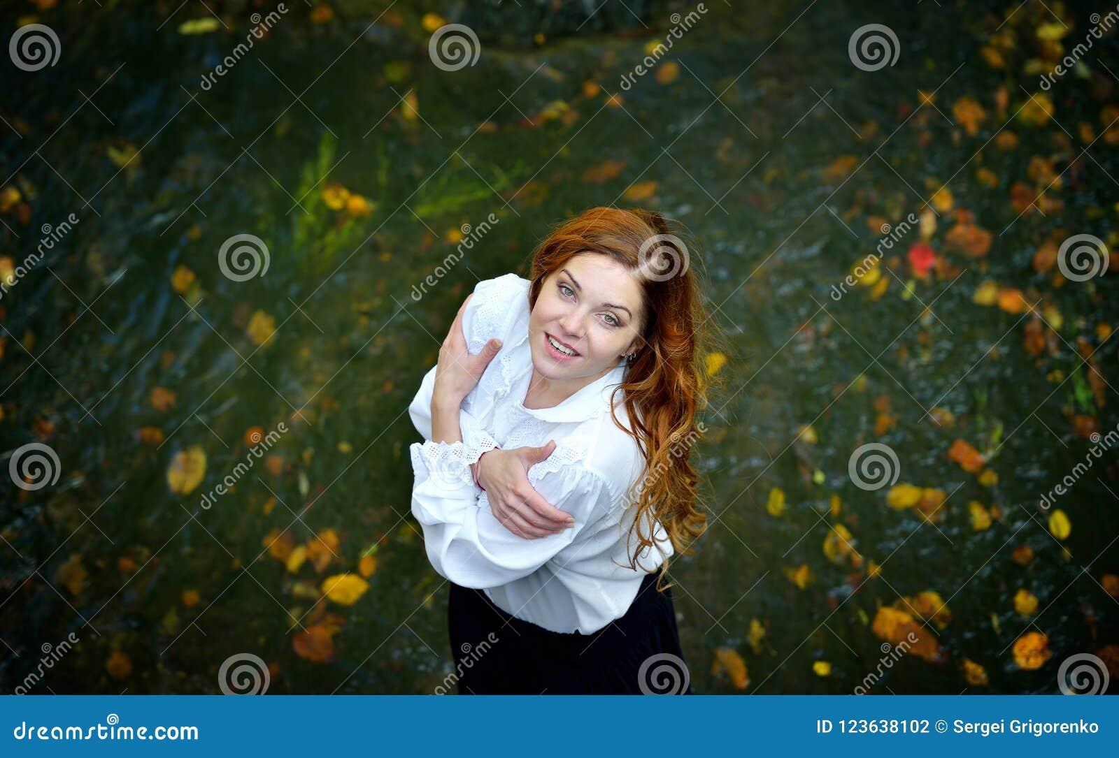 Menina bonita com cabelo longo na camisa branca e na saia preta que estão no rio com folhas de outono e que olham acima
