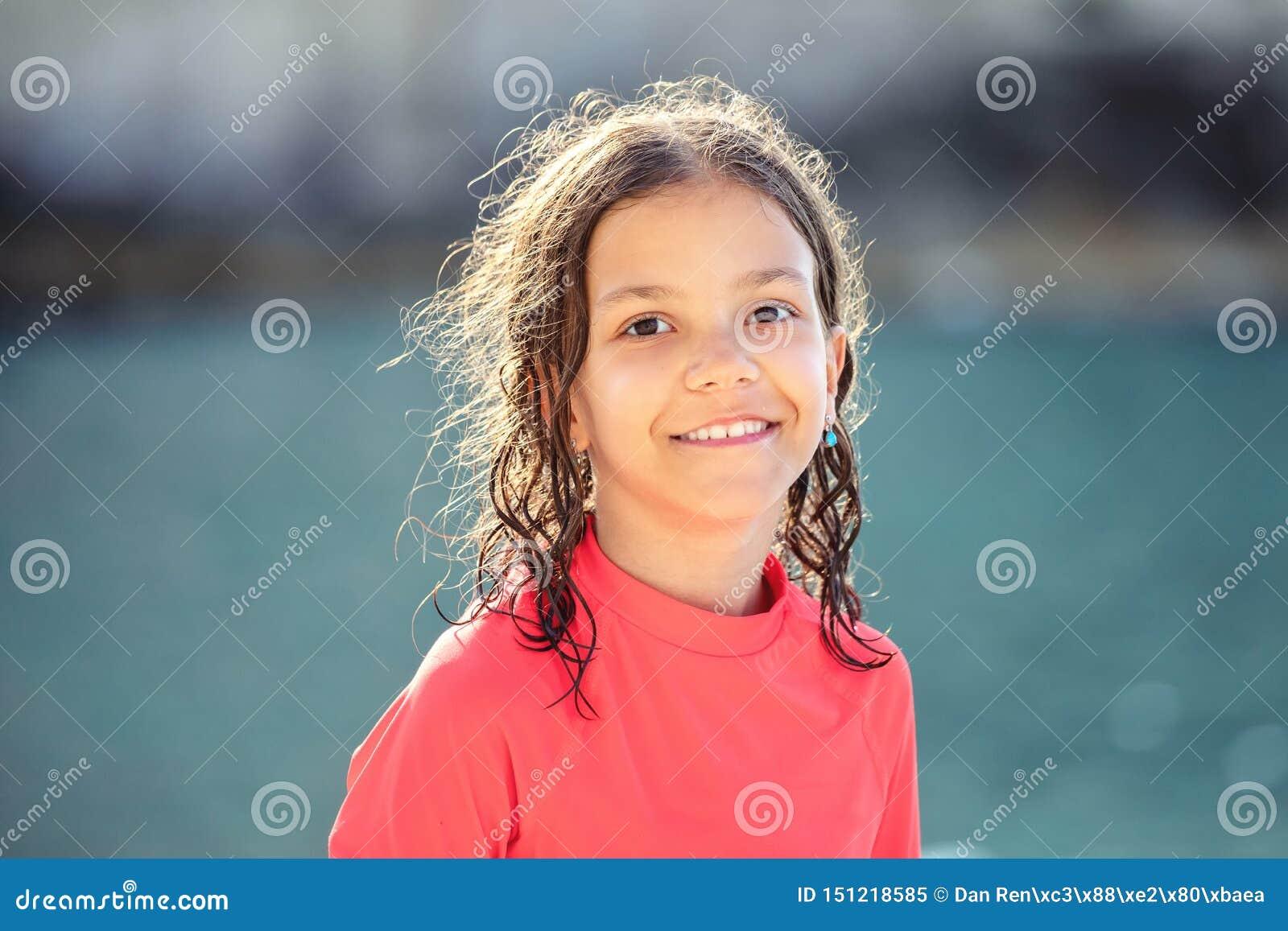 Menina bonita com cabelo molhado que sorri e que olha a câmera na praia durante o por do sol, retrato exterior da criança feliz