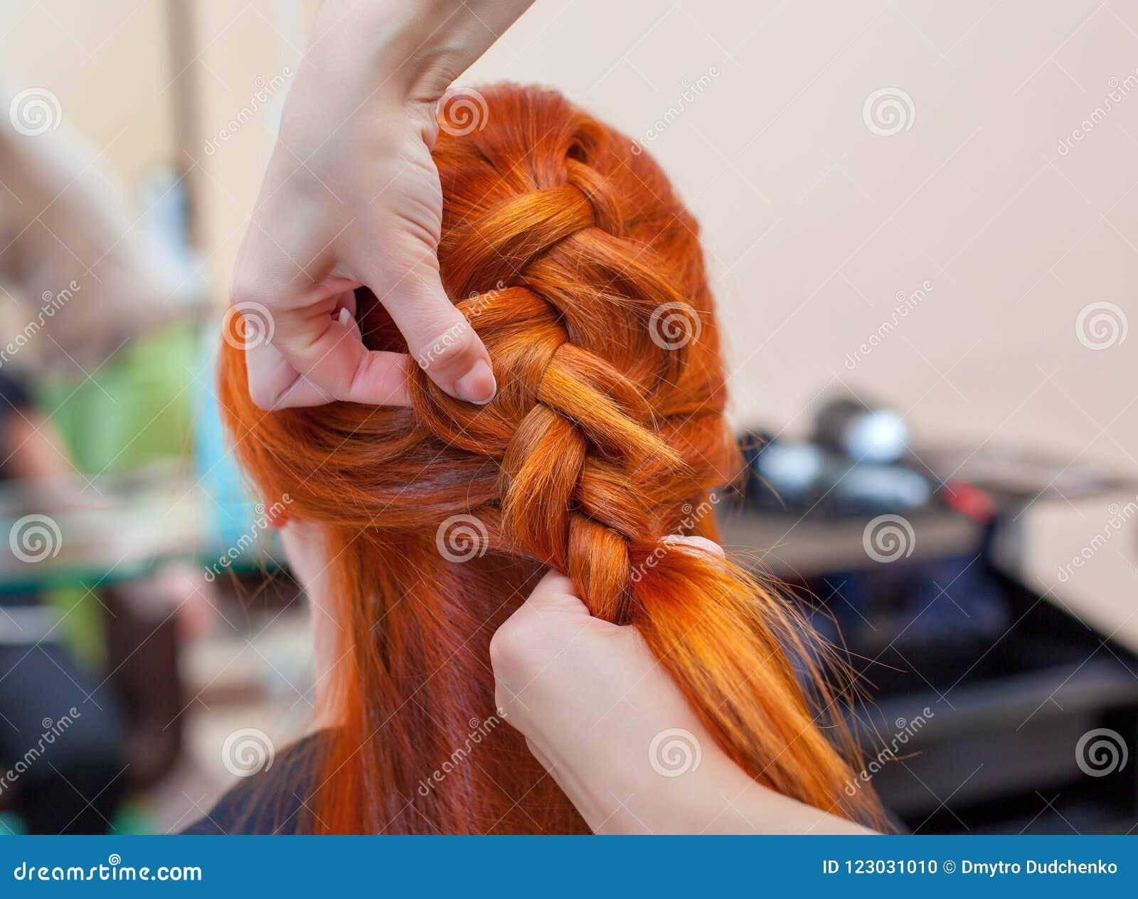 A menina bonita com cabelo vermelho, cabeleireiro tece um close-up da trança, em um salão de beleza