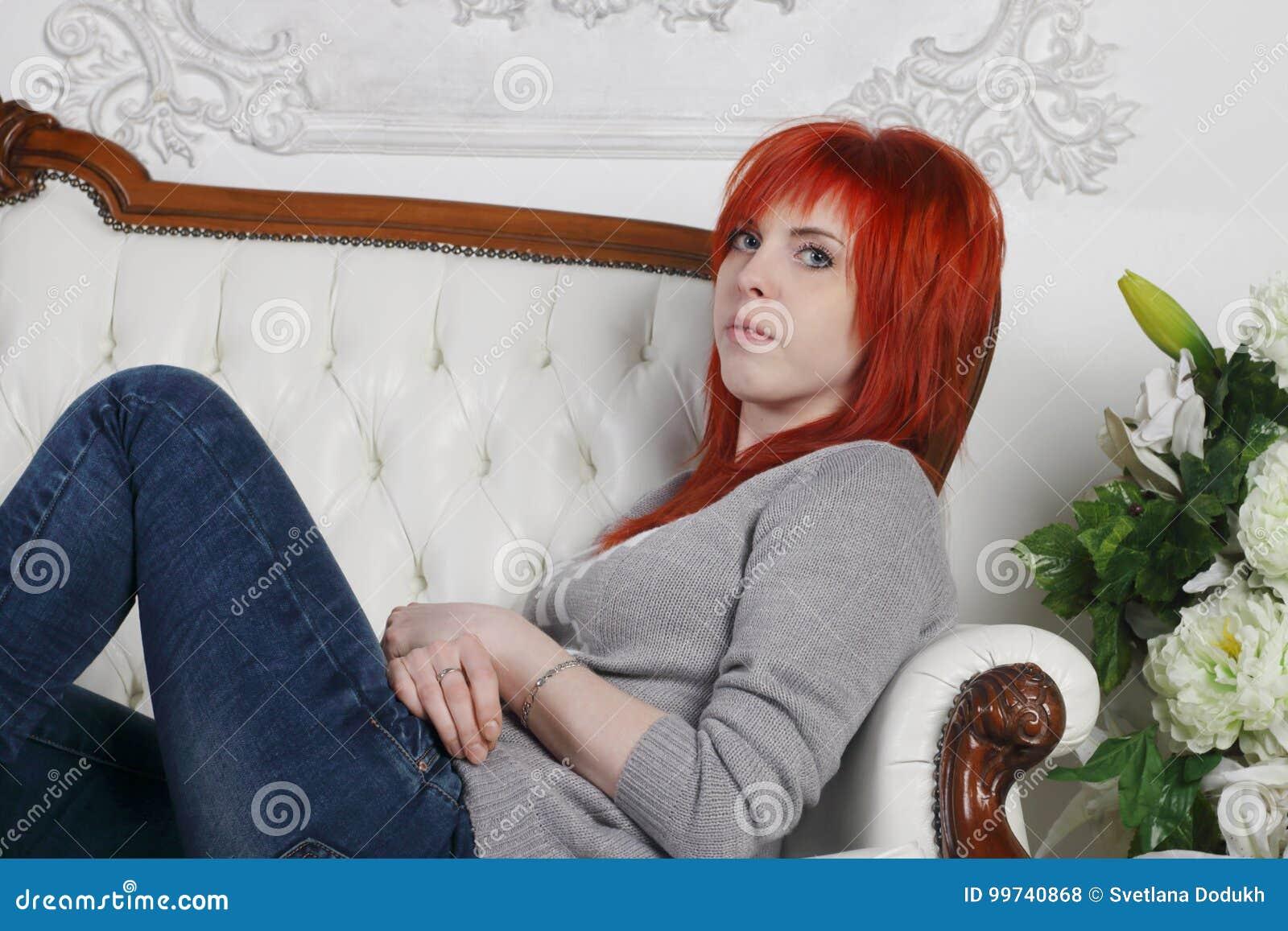 3578432307c7 A menina bonita com cabelo vermelho nos vidros senta-se no sofá branco na  sala branca com flores