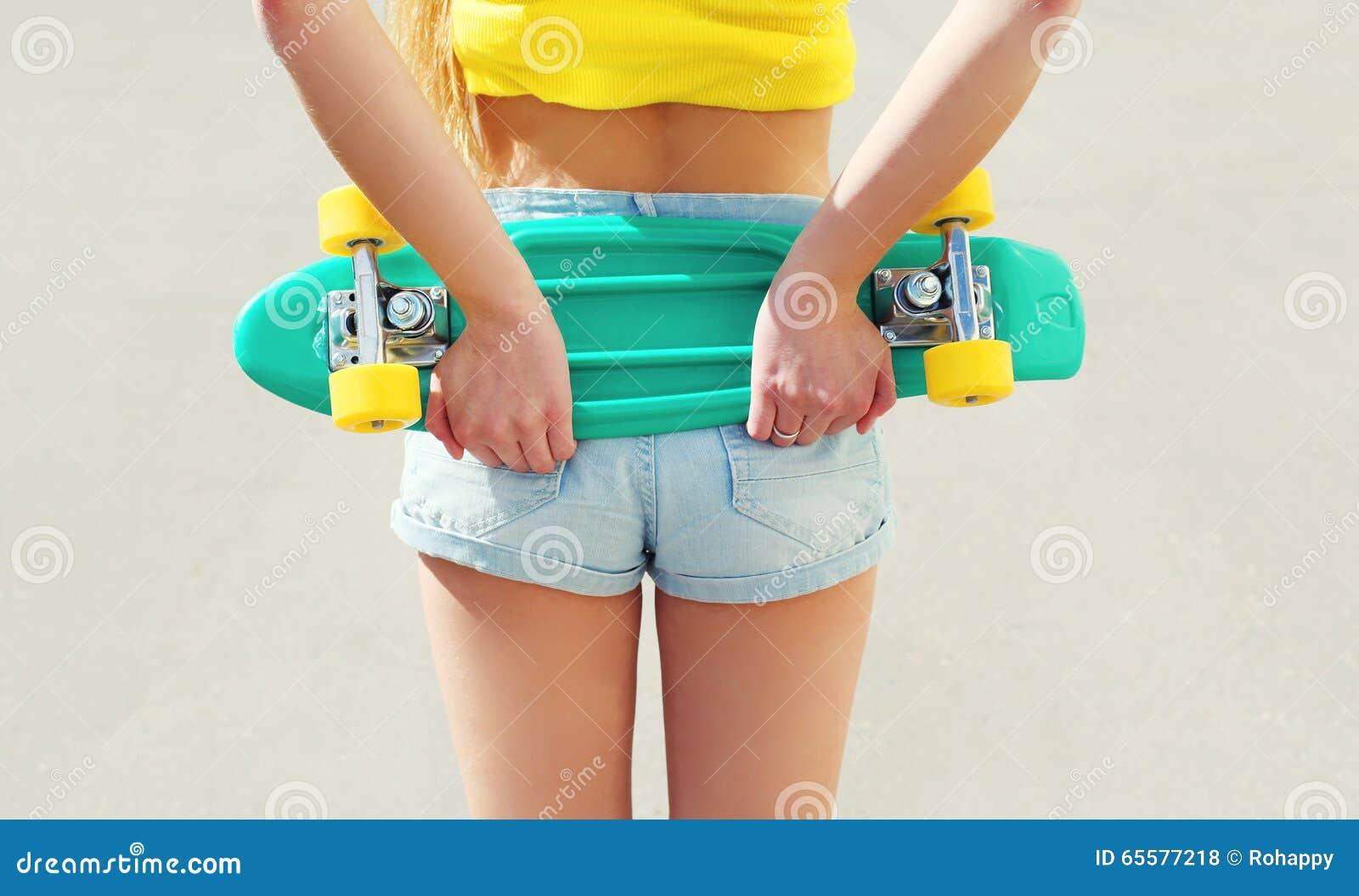 Menina bonita com o skate na opinião do short da parte traseira