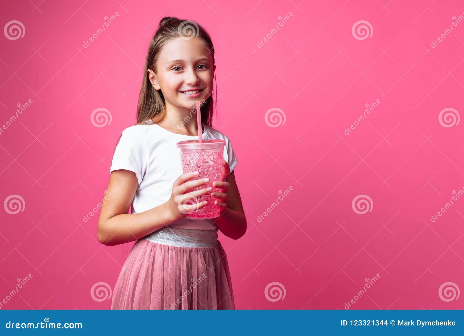 Menina bonita com uma bebida ou cocktail em suas mãos, em um fundo cor-de-rosa, em um estúdio da foto, close-up