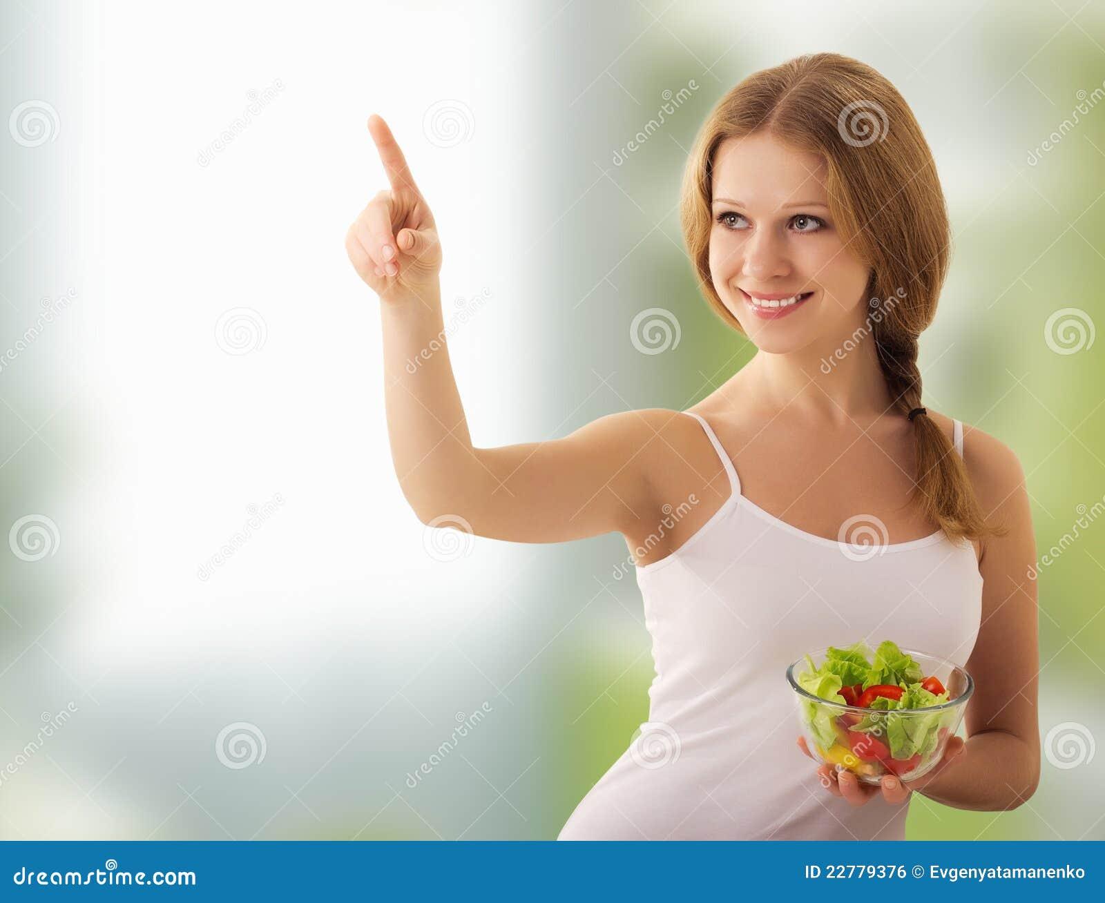 A menina bonita com uma salada escolhe o alimento saudável