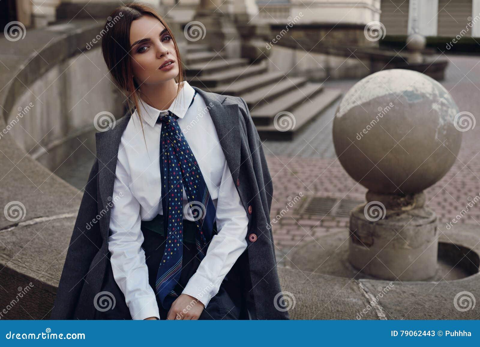 Menina bonita da forma na roupa elegante que levanta na rua