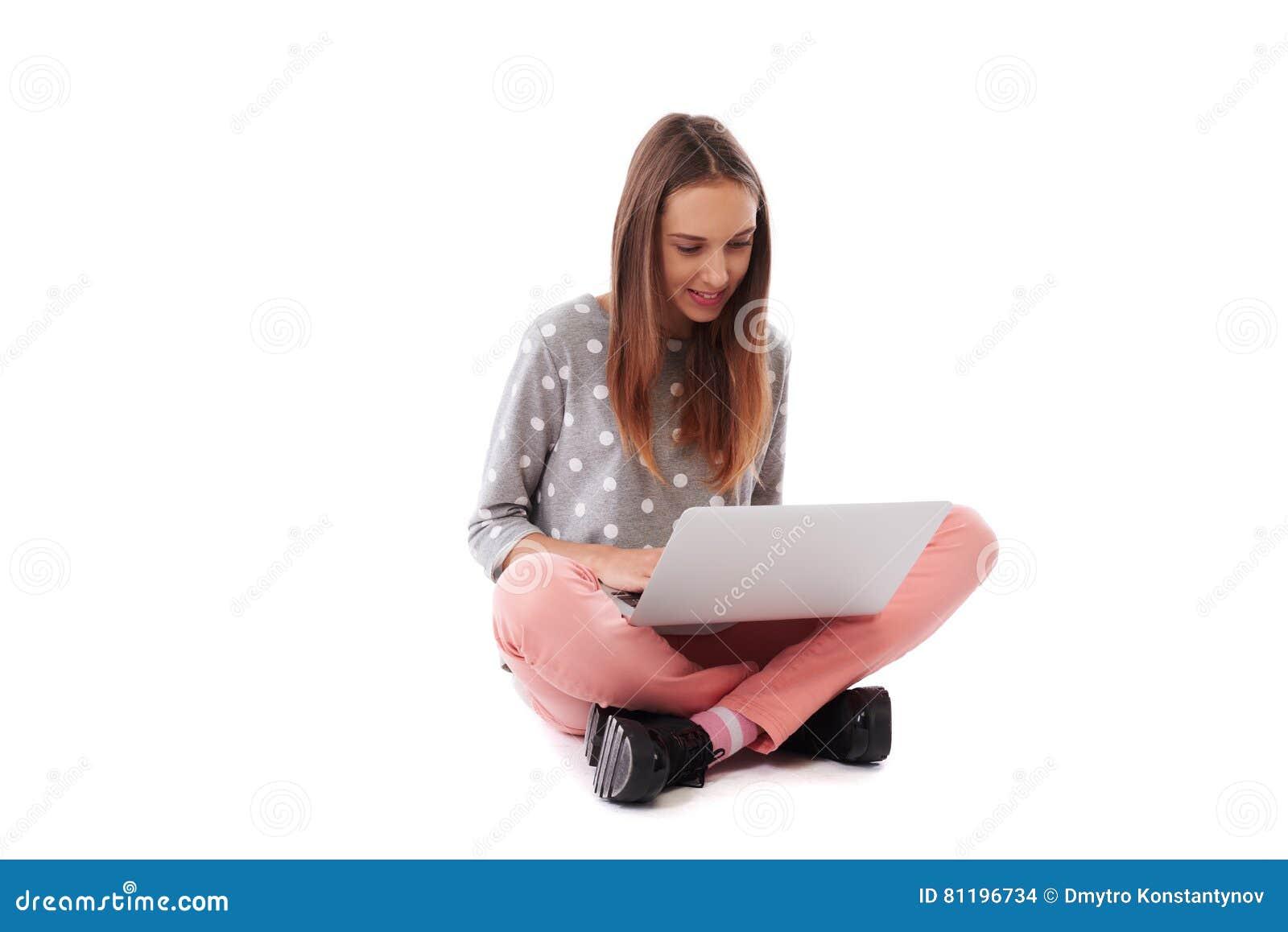 Menina bonita de sorriso que senta-se no assoalho e em guardar o portátil o