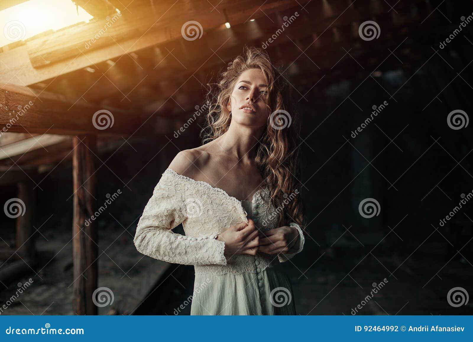 Menina bonita dentro no vestido branco do vintage com o cabelo encaracolado que levanta no sótão Mulher no vestido retro Emoção s