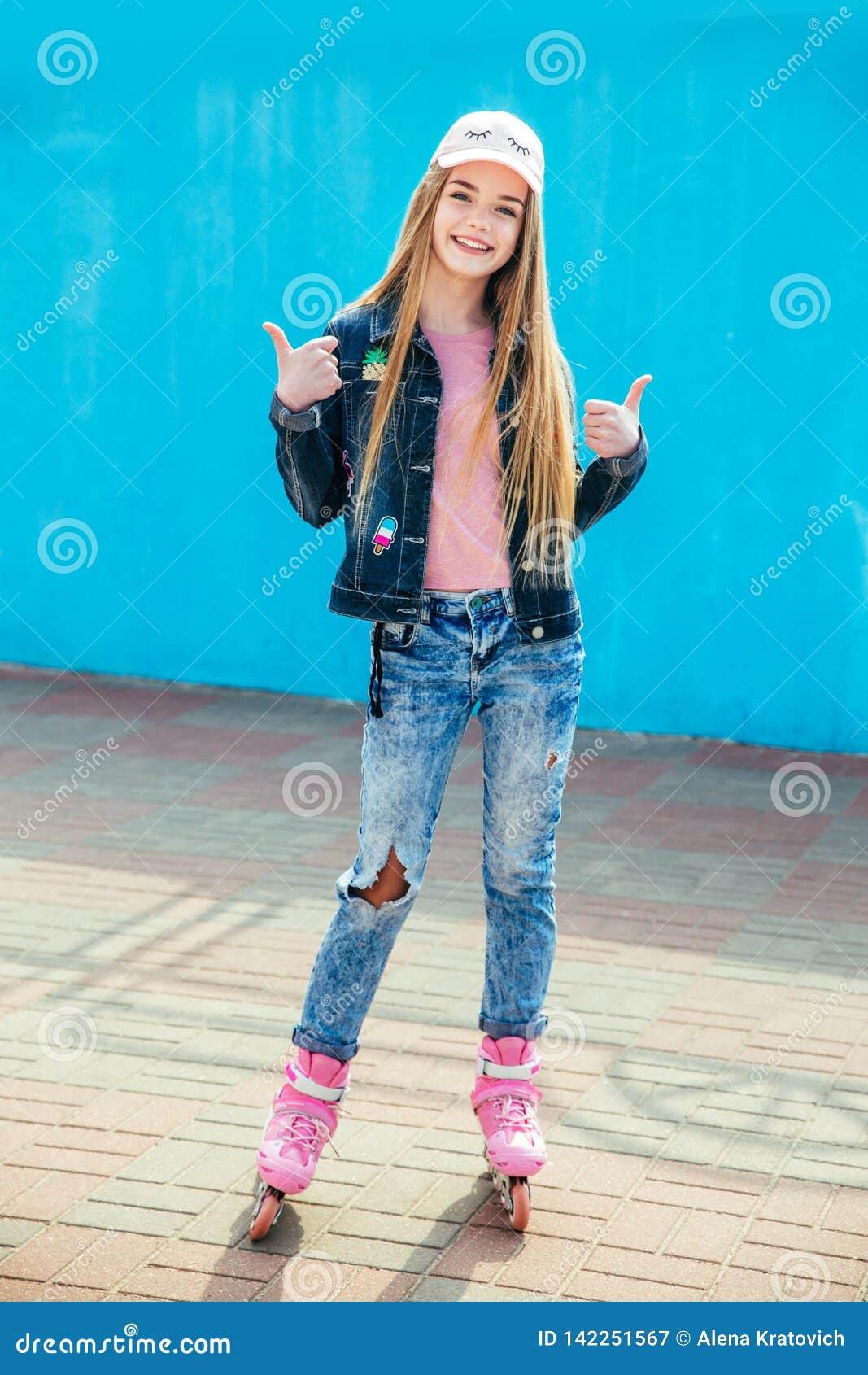 Menina bonita do adolescente no tampão que olha a câmera e que sorri ao estar em rolos no parque do patim