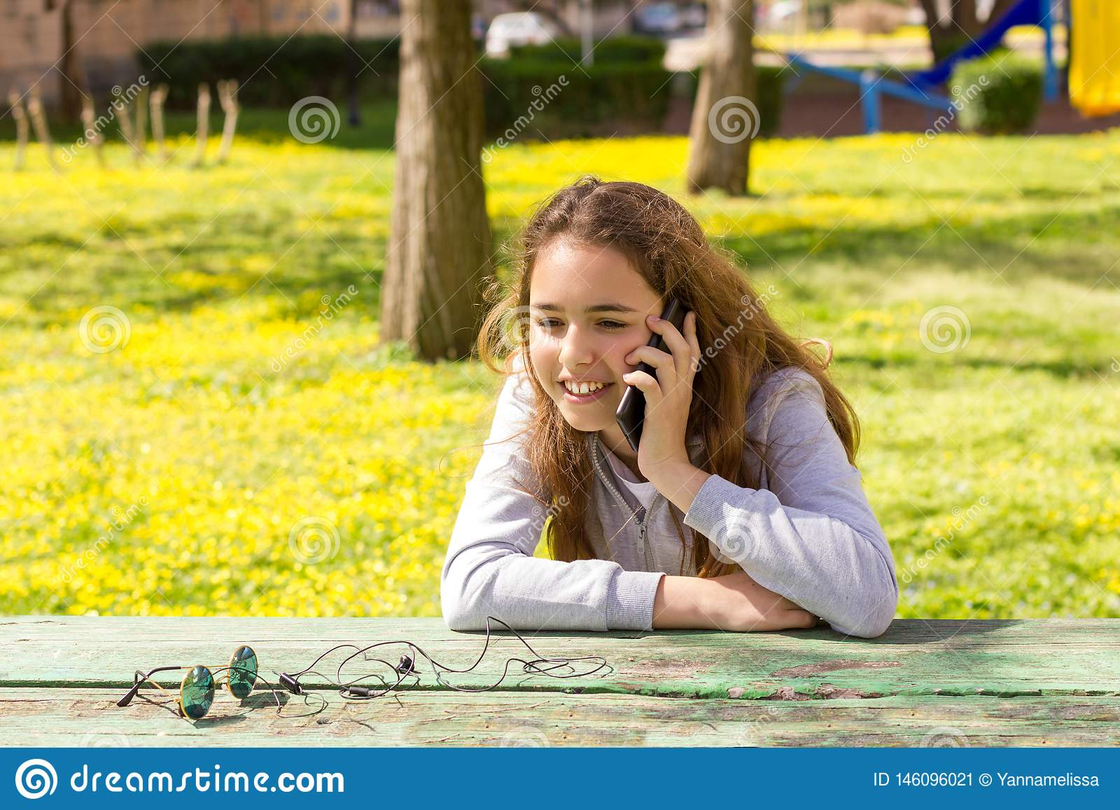 Menina bonita do adolescente que fala pelo smartphone m?vel do cellpfone no parque do ver?o