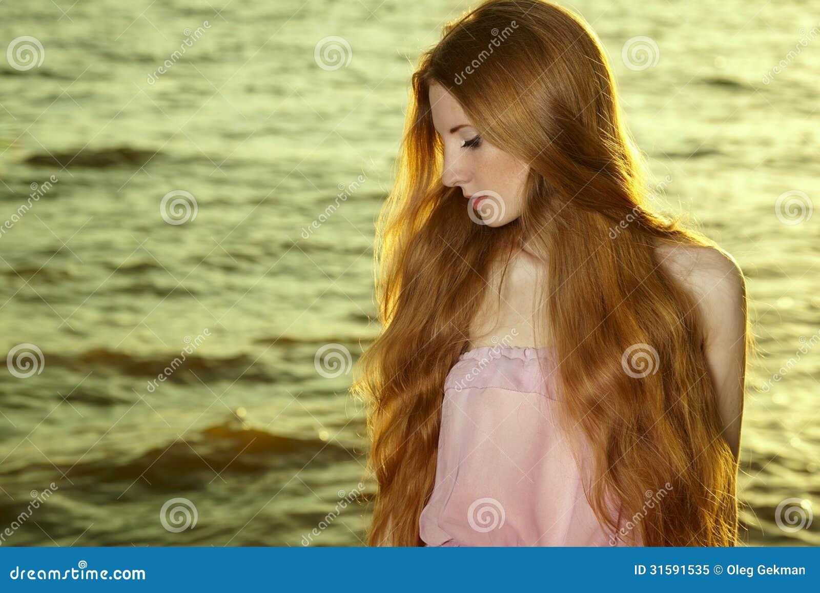 Menina bonita do ruivo na lagoa