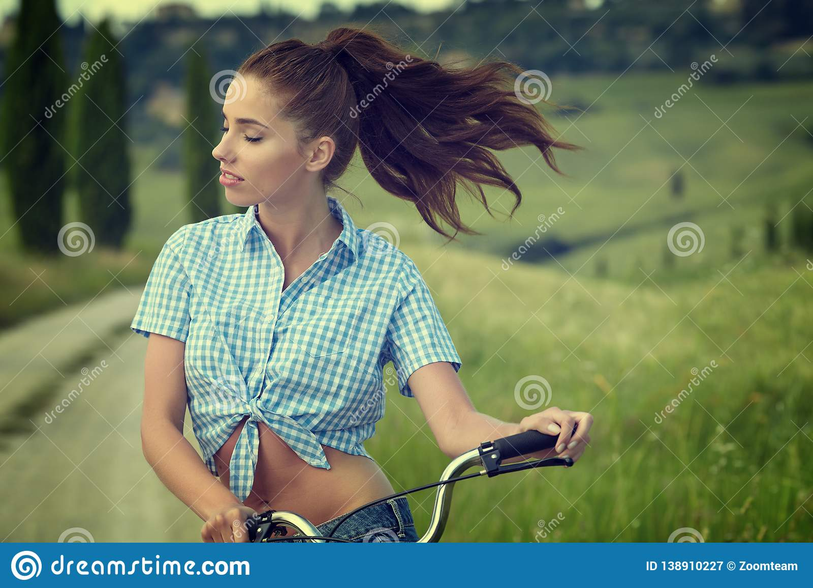 Menina bonita do vintage que senta-se ao lado da bicicleta, horas de verão