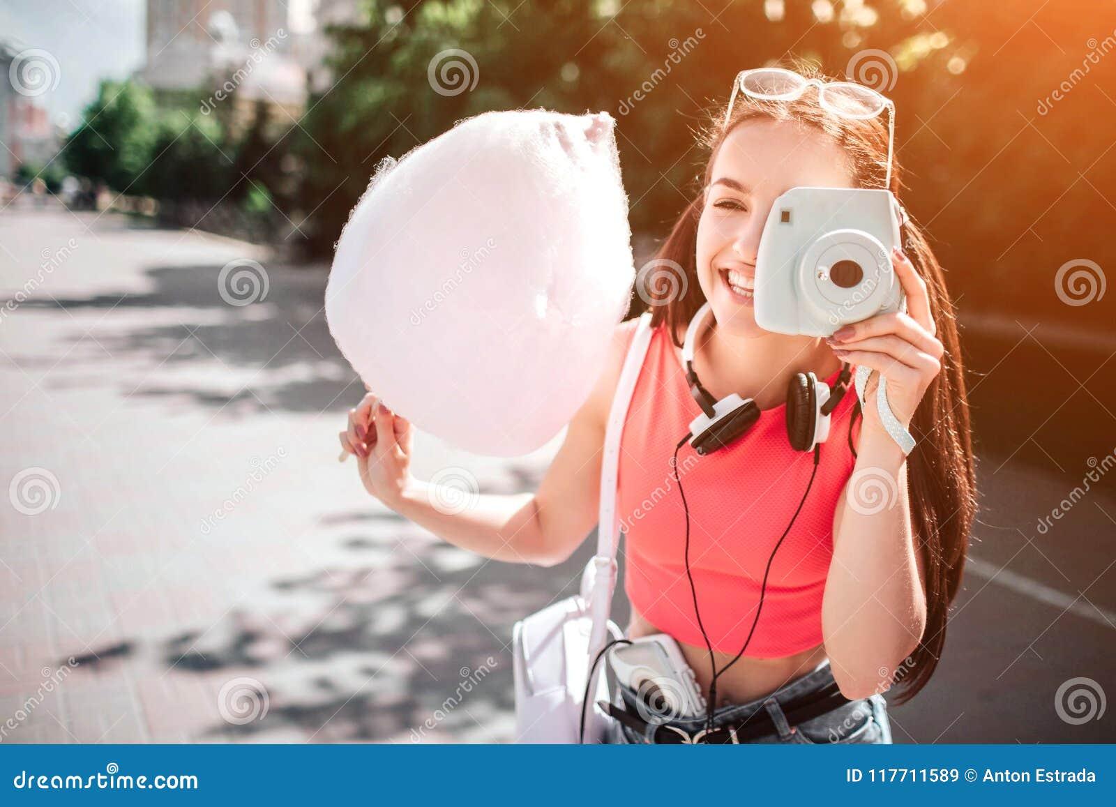 A menina bonita e lindo é estando e de levantamento como está tomando a imagem com sua câmera branca Igualmente a menina é