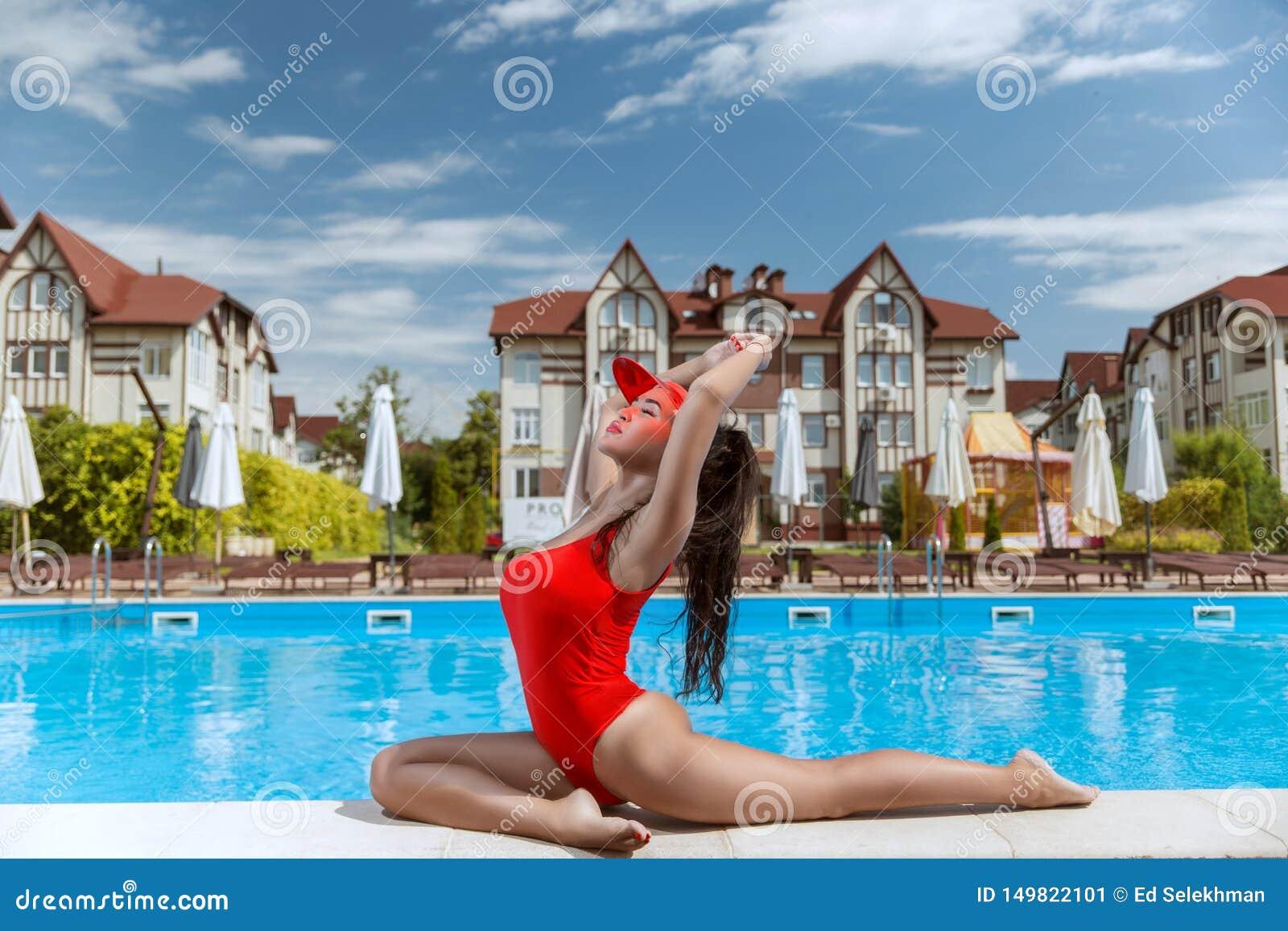 Menina bonita em um maiô vermelho em um hotel bonito perto da associação
