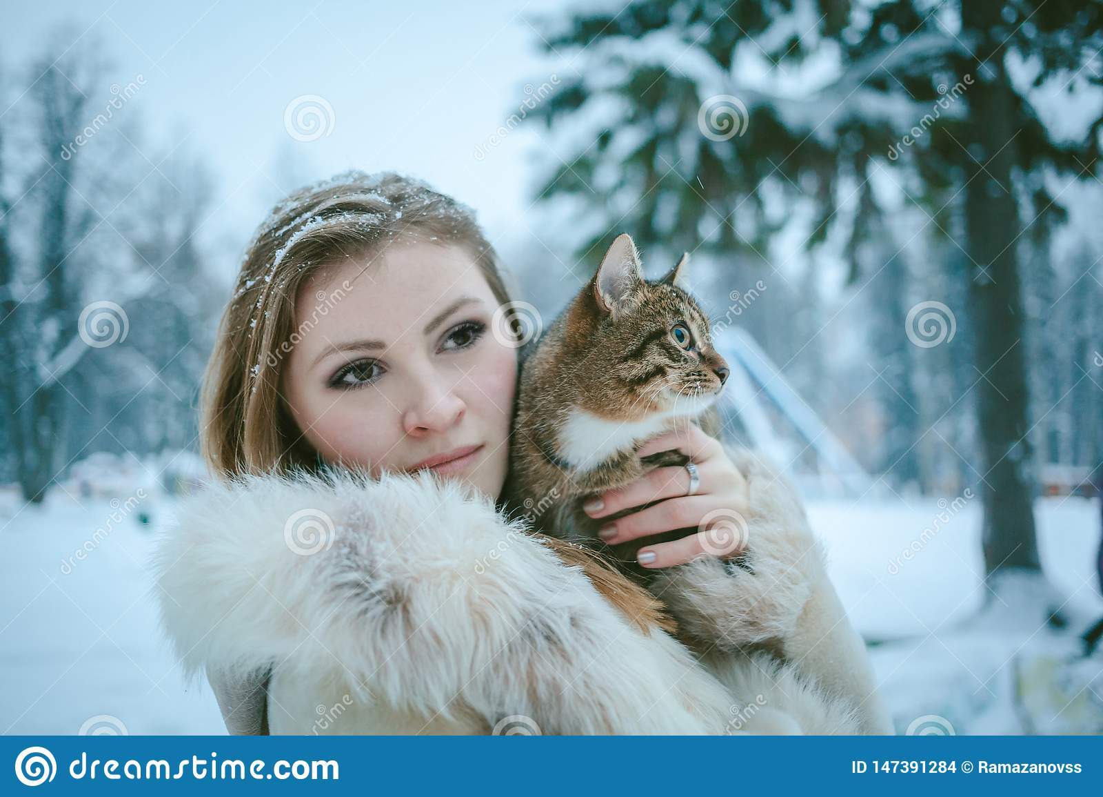 Menina bonita em um revestimento curto bege com o cabelo de fluxo que guarda um gato