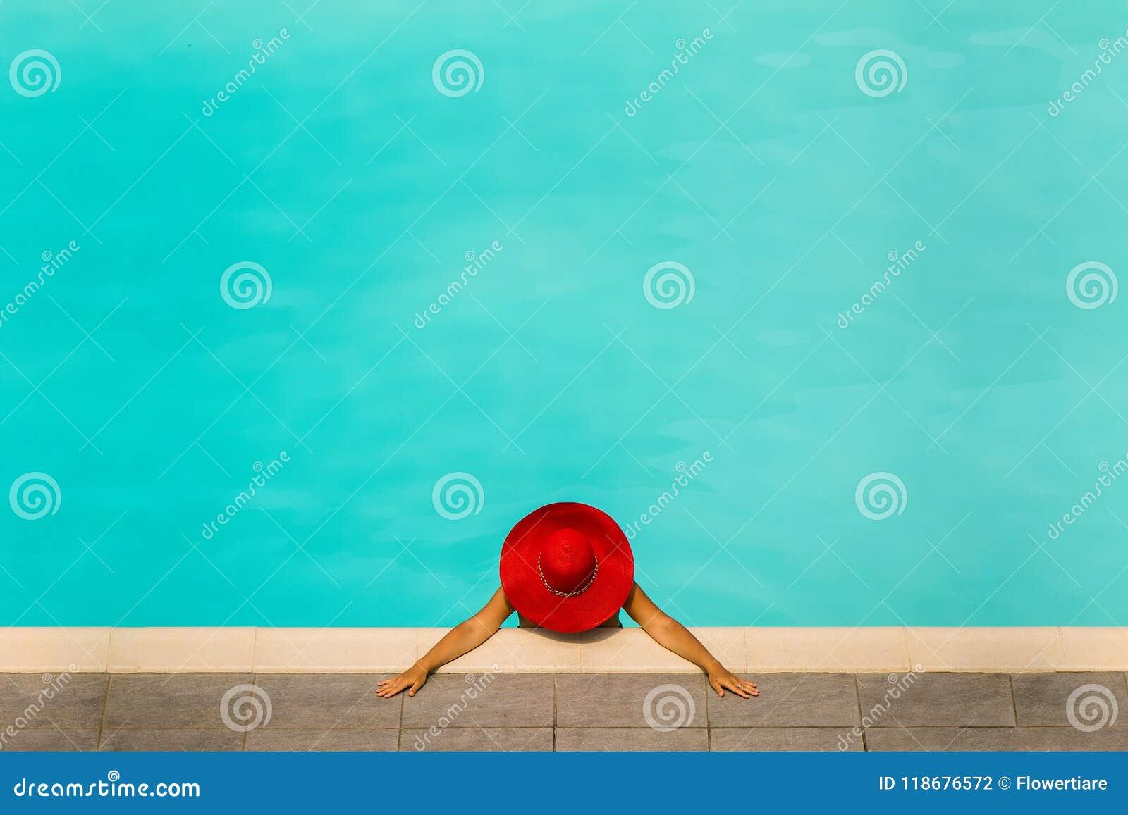 Menina bonita em um roupa de banho e em um chapéu vermelho em uma associação de água azul
