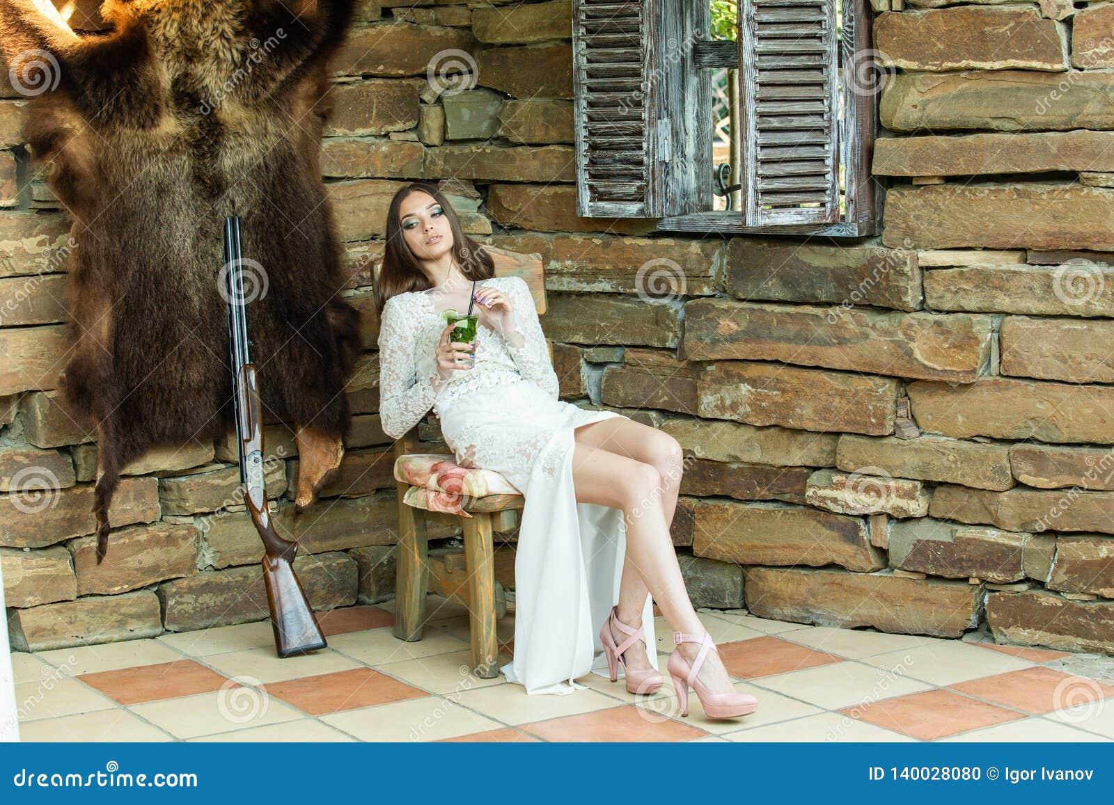 A menina bonita em um vestido branco está bebendo o mojito que senta-se ao lado de um rifle de caça