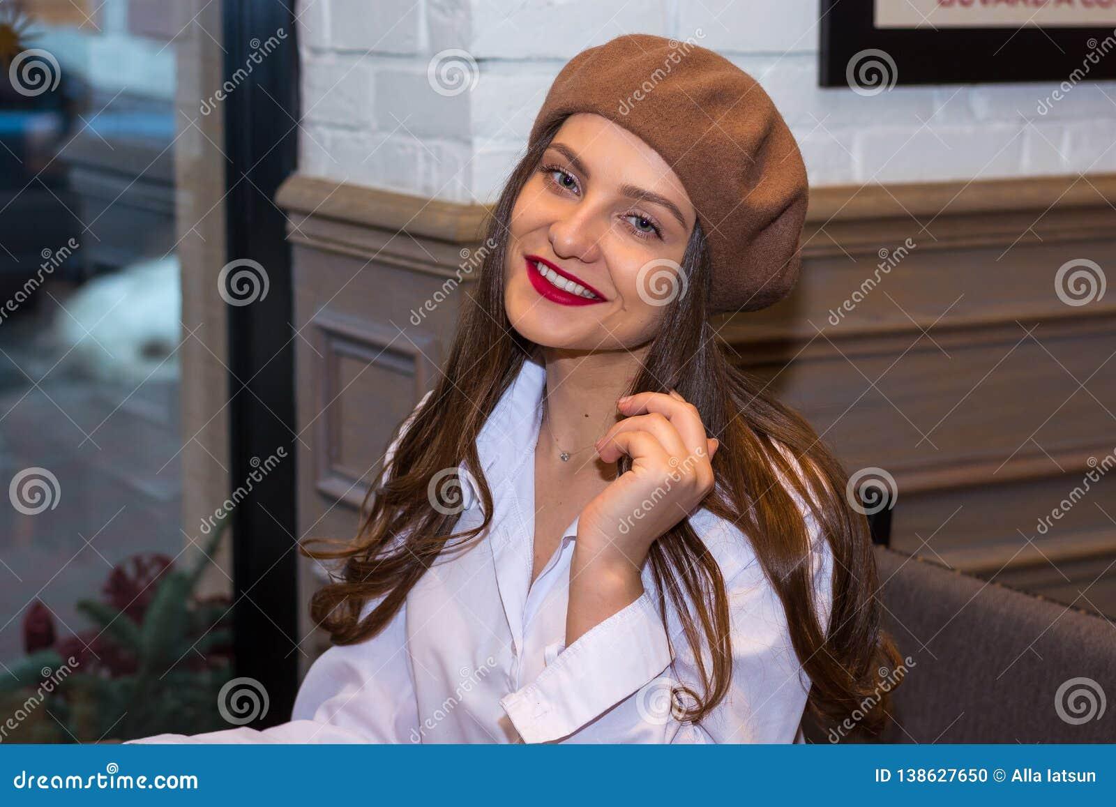 A menina bonita em uma boina senta-se perto da janela em um café
