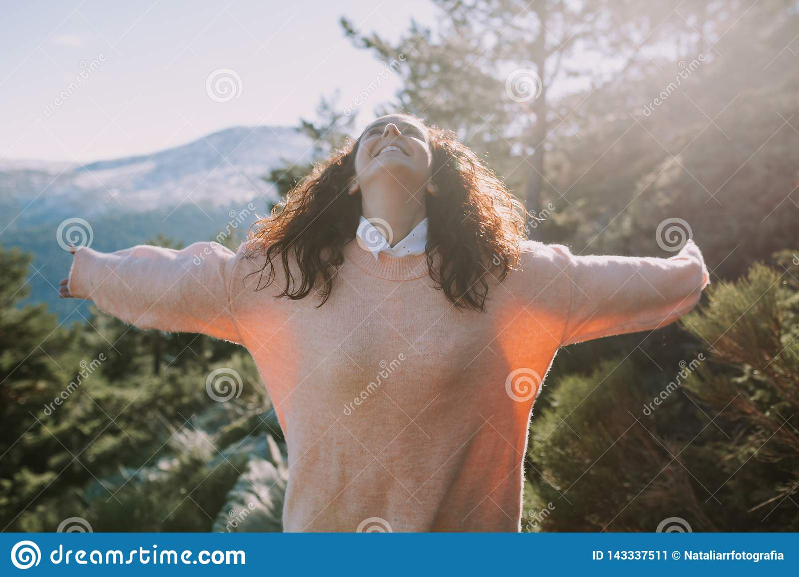 A menina bonita em uma camiseta colorida coral espalha seus braços com uma cara feliz