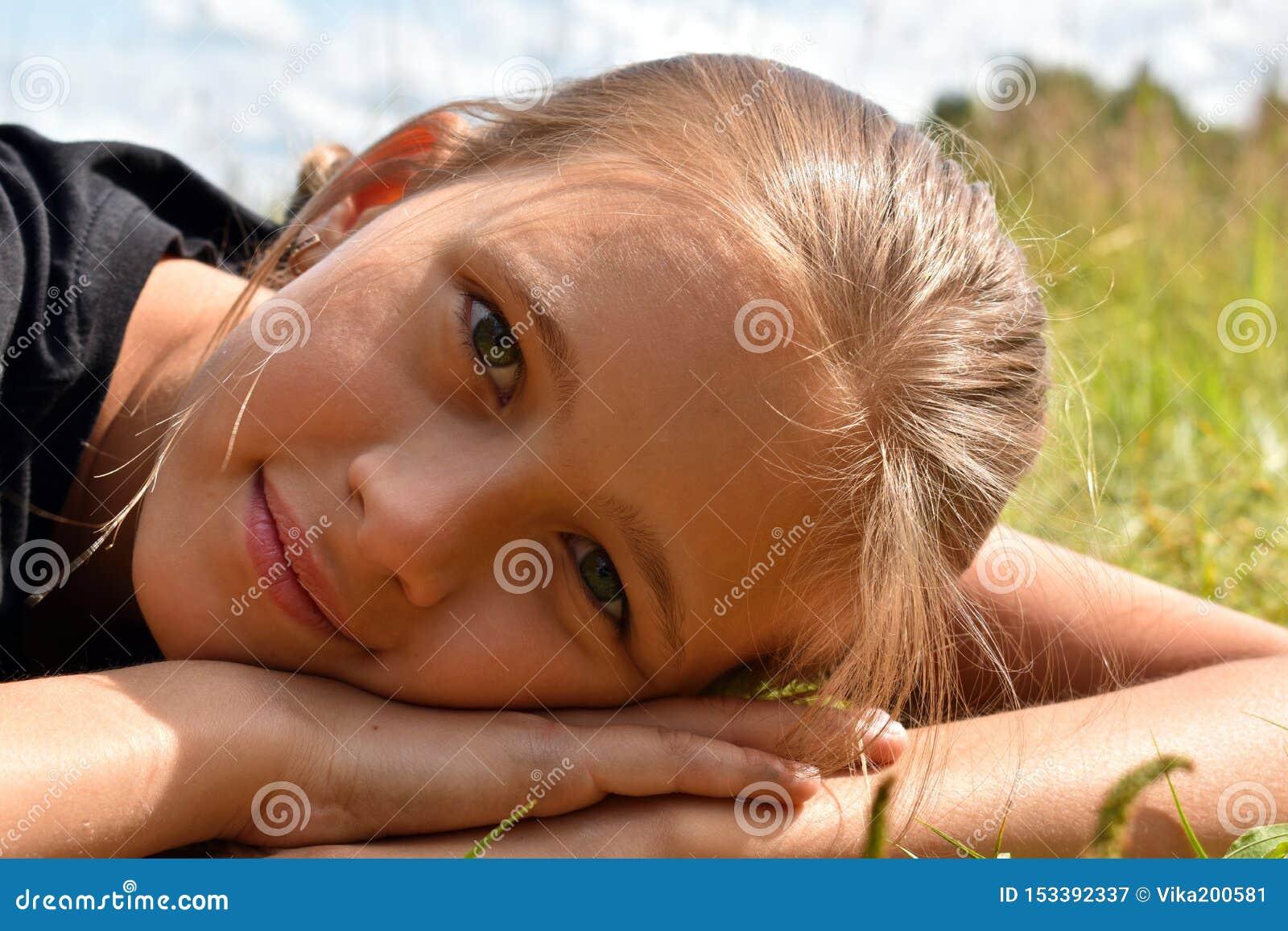 Menina bonita em uma grama verde no verão
