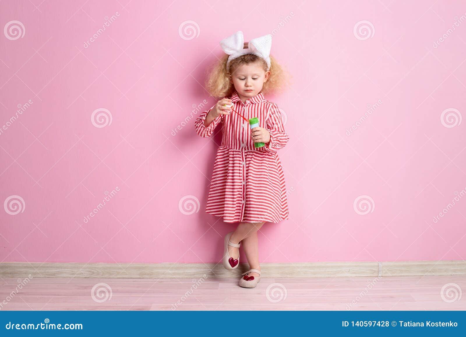 A menina bonita em umas orelhas vermelhas e brancas listradas do vestido e do coelho em sua cabeça infla as bolhas de sabão que e