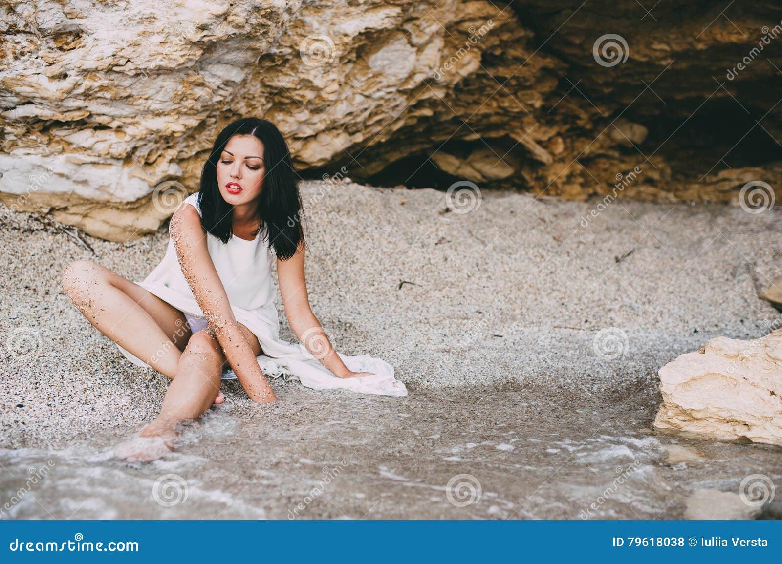 A menina bonita encontra-se em uma garganta de pedra na praia