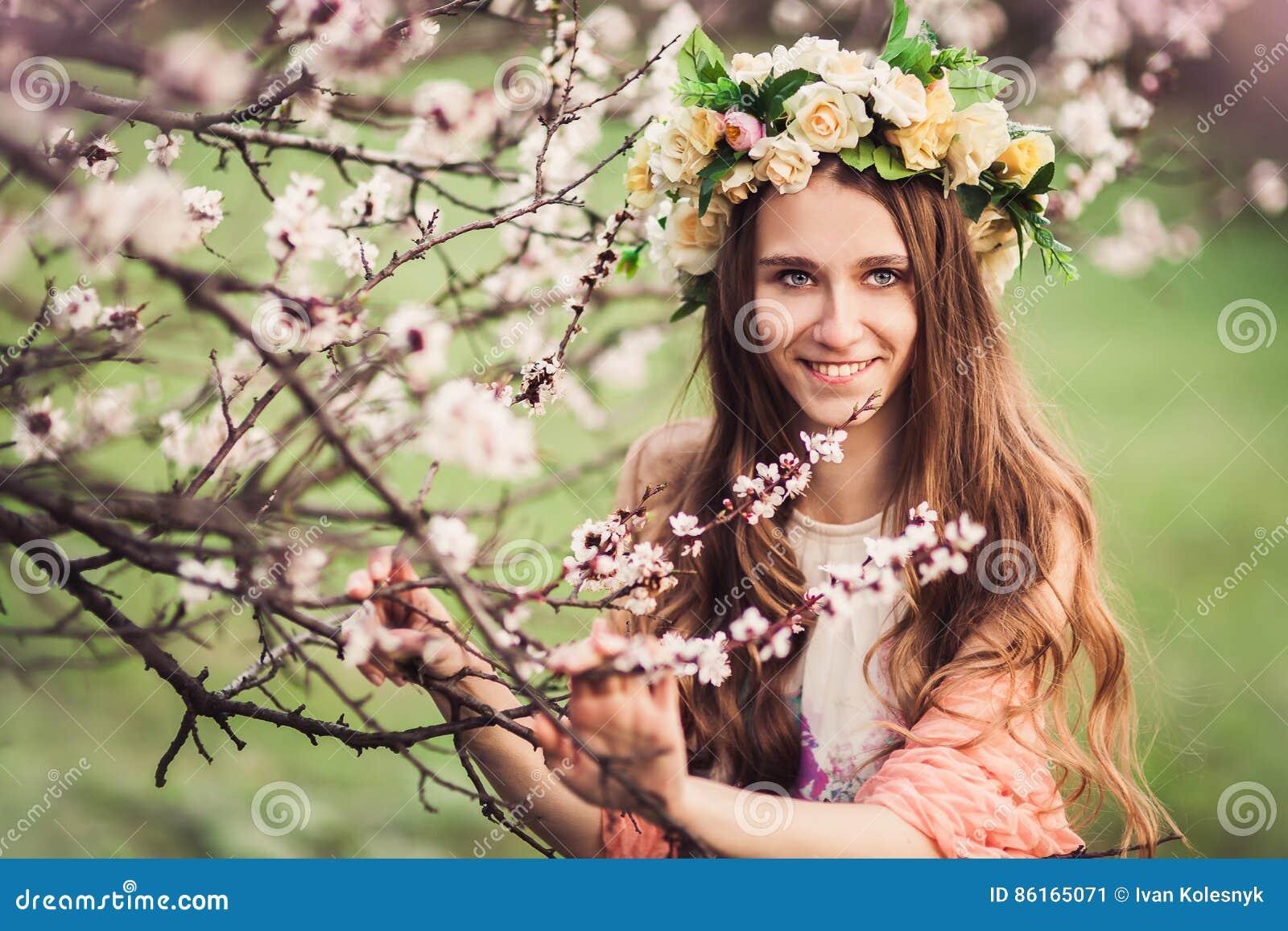 Menina bonita entre os ramos da árvore de cereja da flor